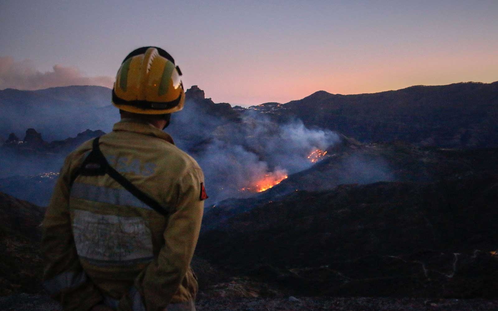 A firefighter observes flames rising from a forest fire near the village of Ayacata in Tejeda on the island of Gran Canaria on August 20, 2019.