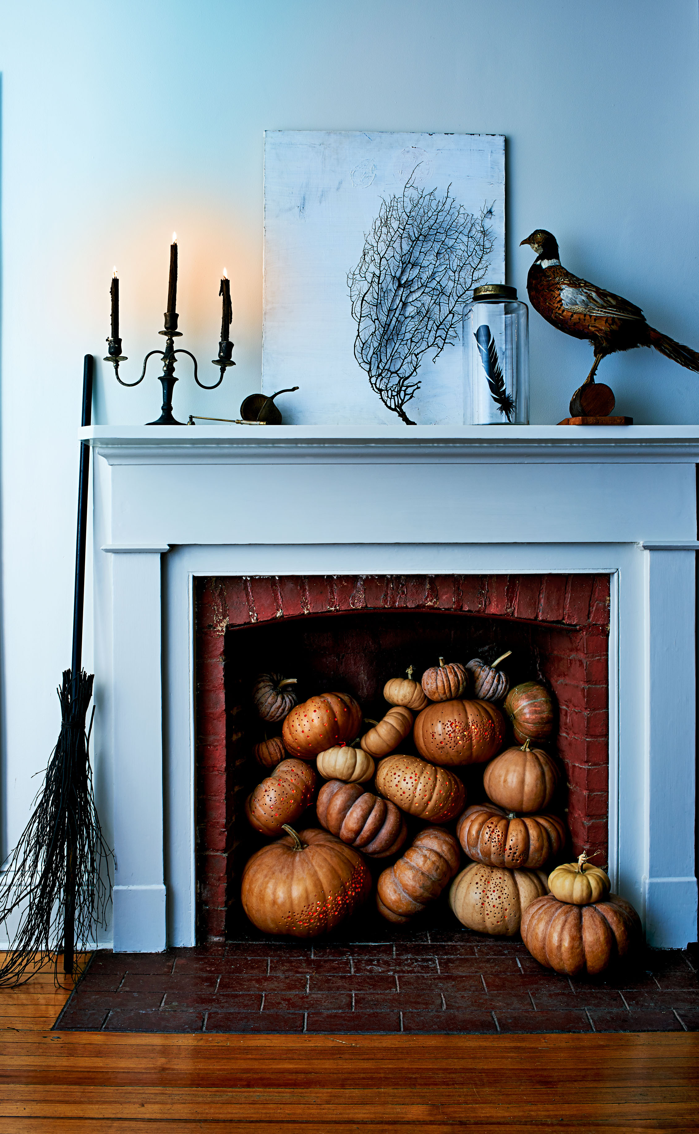 drilled pumpkins in a fireplace
