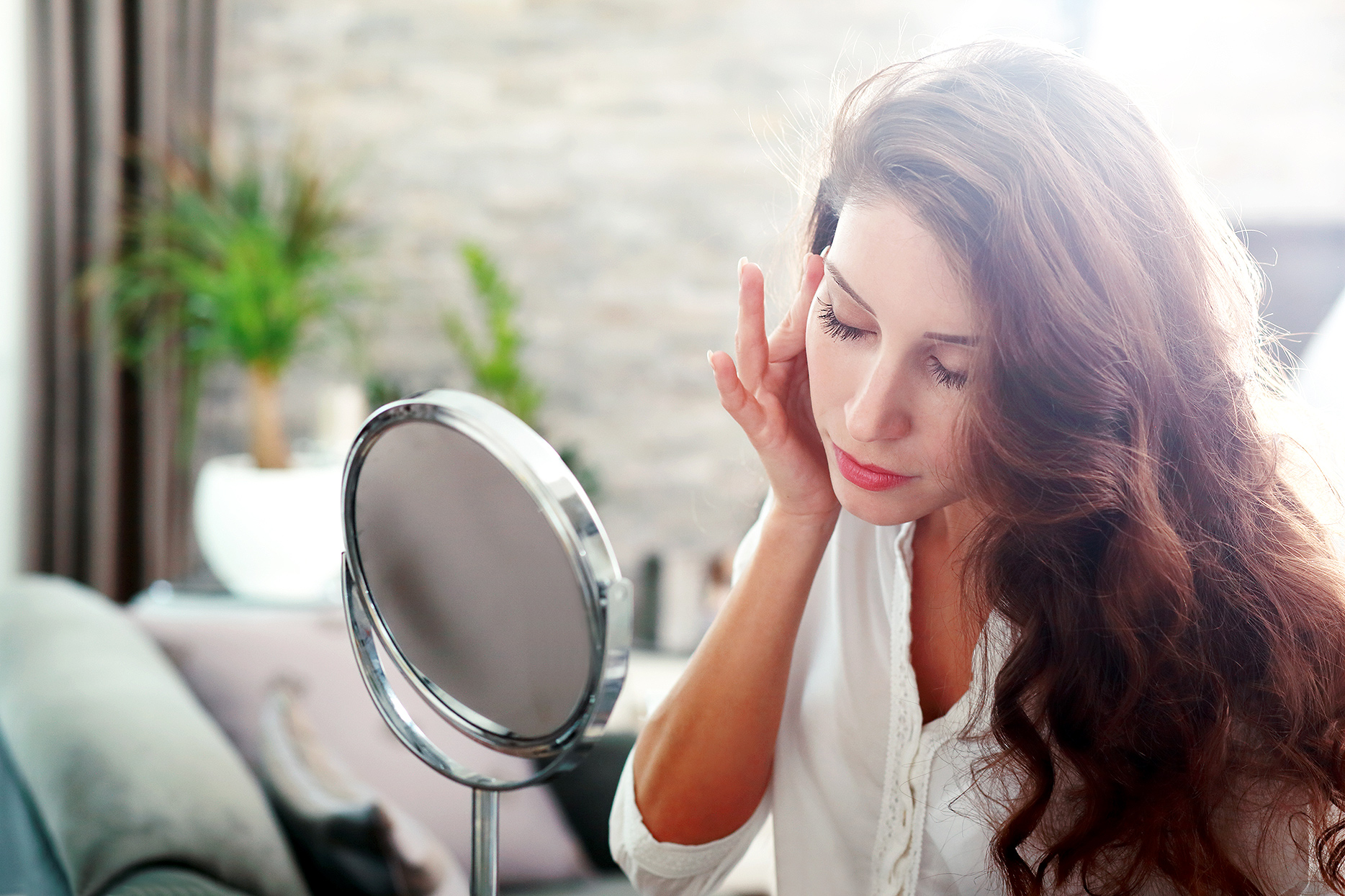 brunette woman touching face and looking into mirror
