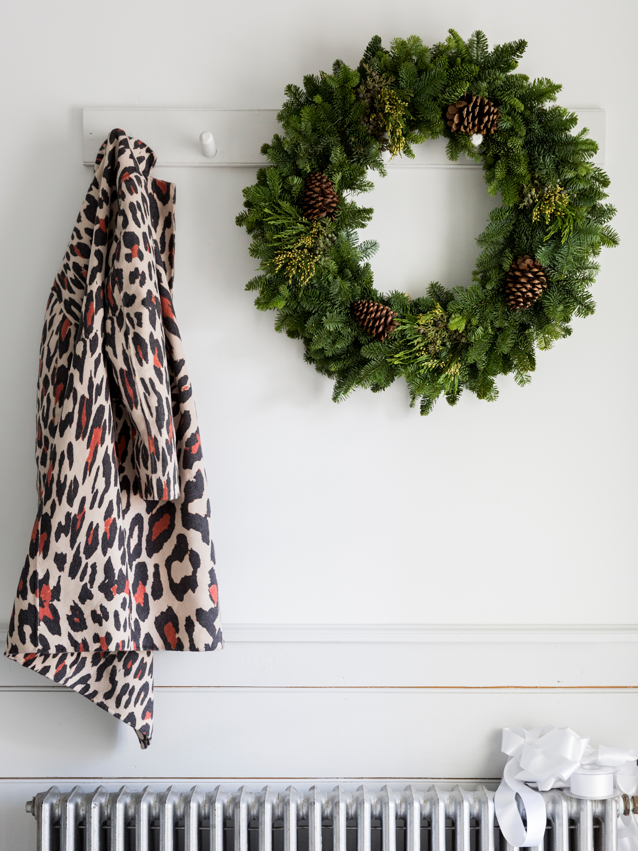 greenery wreath with pinecones hanging on wall