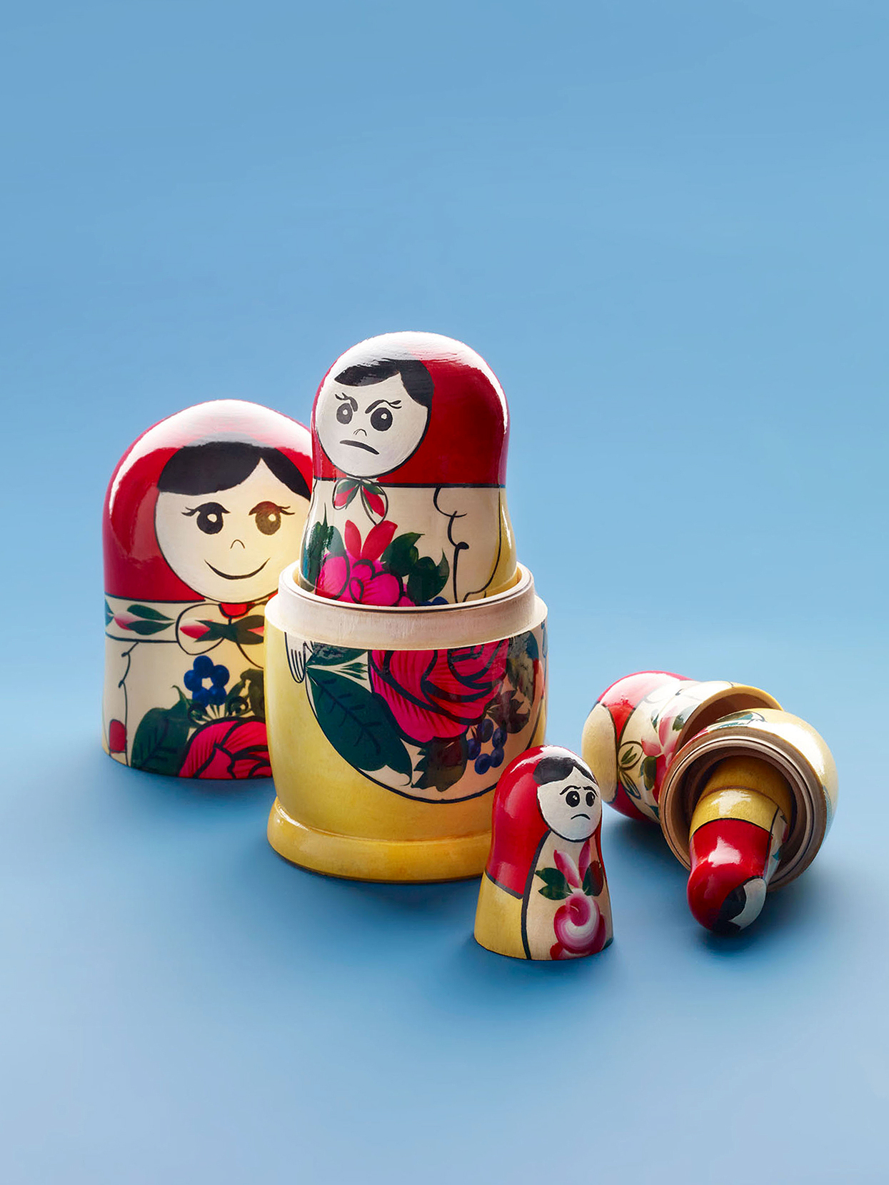 Russian nesting dolls with various facial expressions on blue