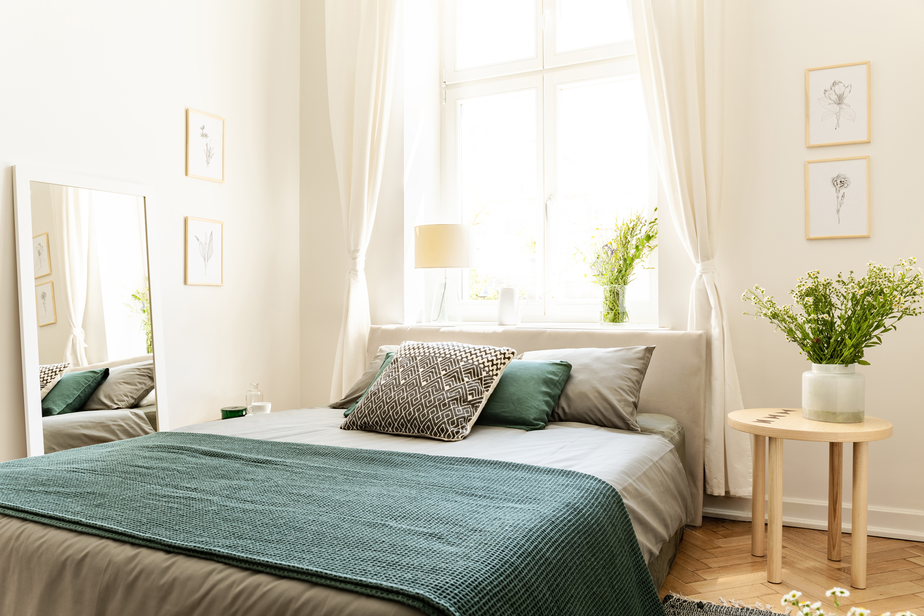 sunny bedroom with vase of daisies on nightstand