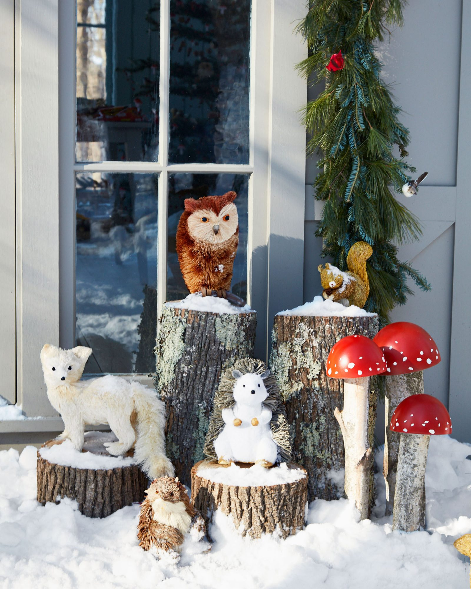 various woodland creatures on snowy logs outside cottage