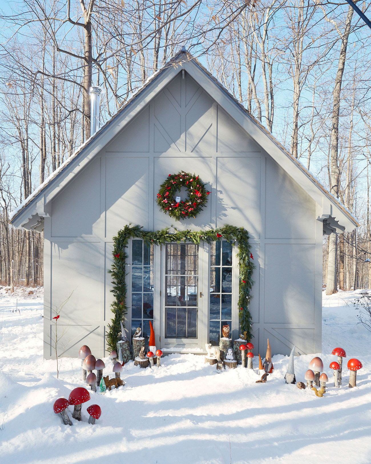 Christmas decorated gray cottage exterior woodland creatures in snow