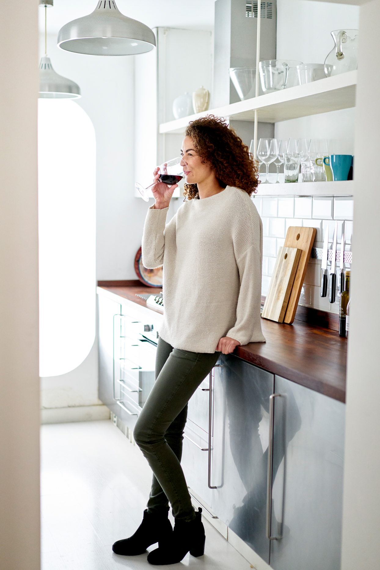 woman standing in kitchen drinking red wine leaning on the counter