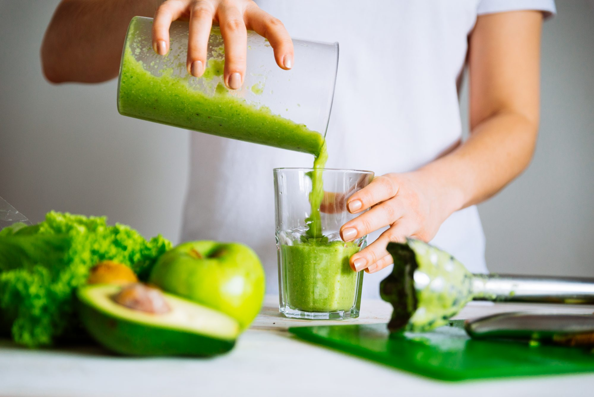 woman making green smoothie with avocado and apples
