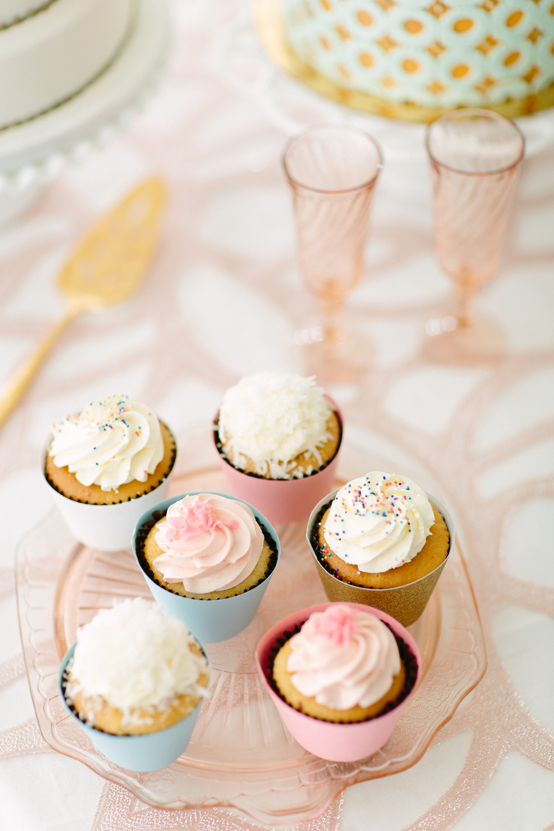 vanilla frosted cupcakes with rainbow and pink sprinkles