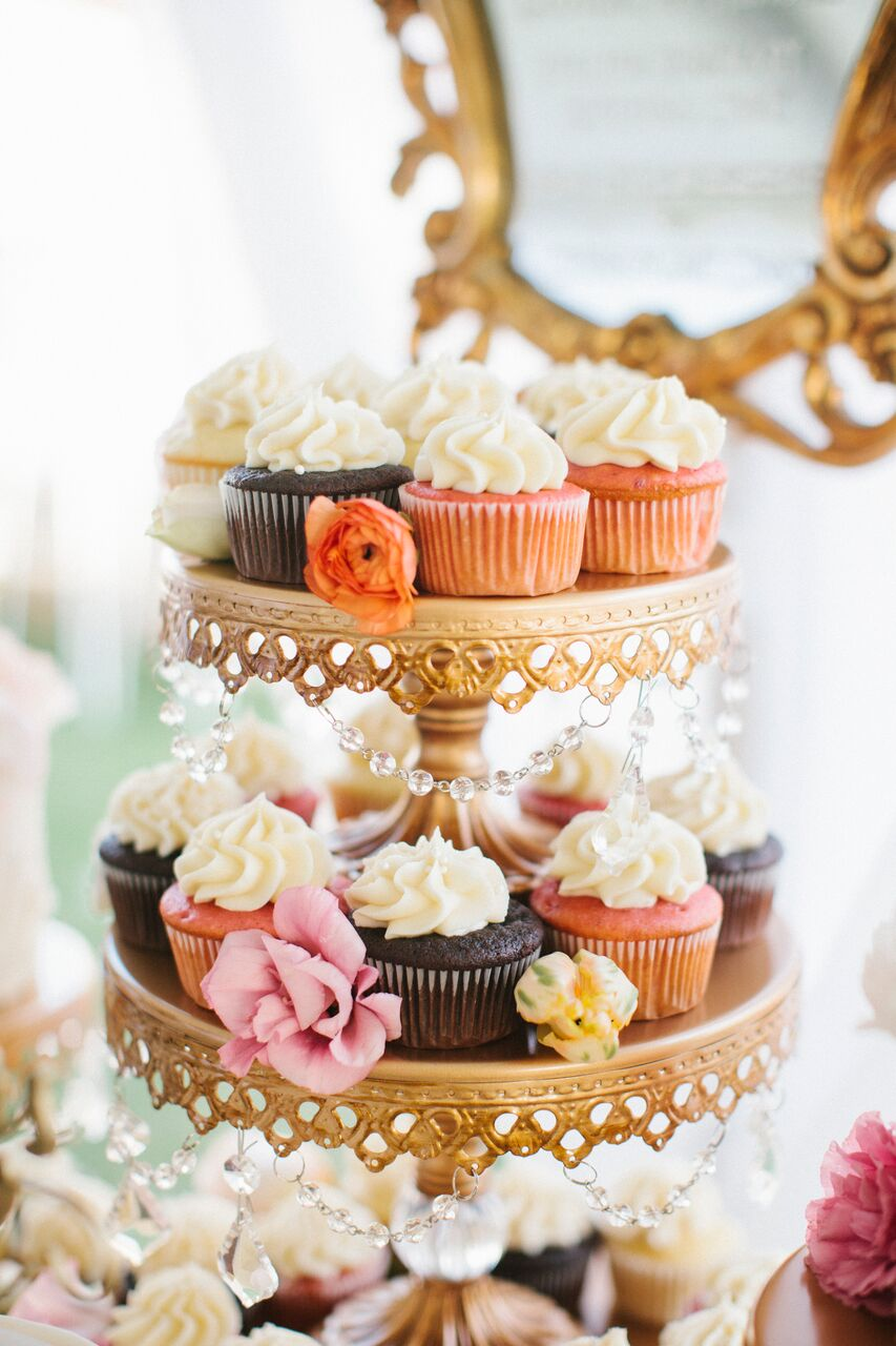 chocolate and orange cupcakes on a gold stand