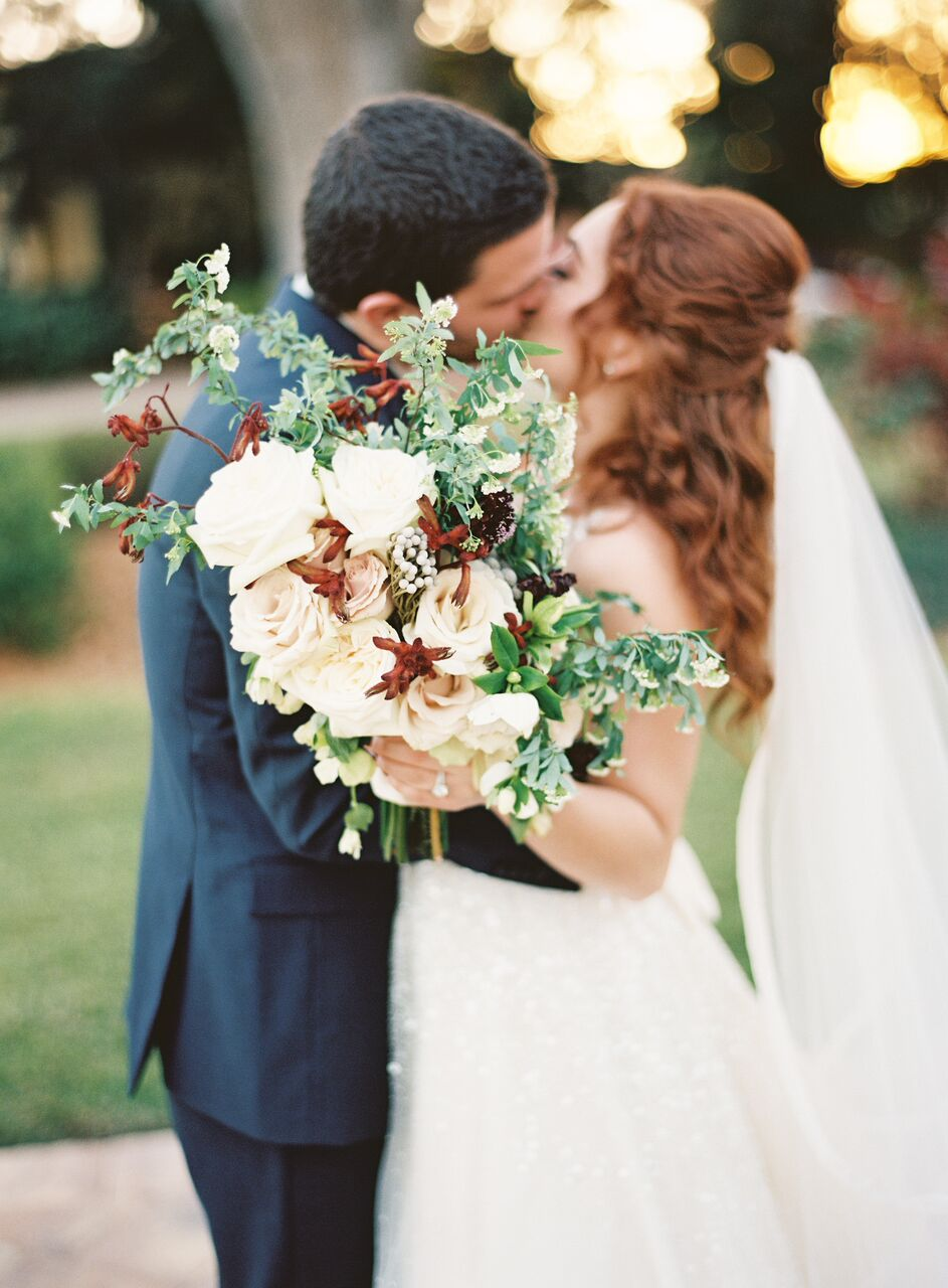 couple kissing with bouquet