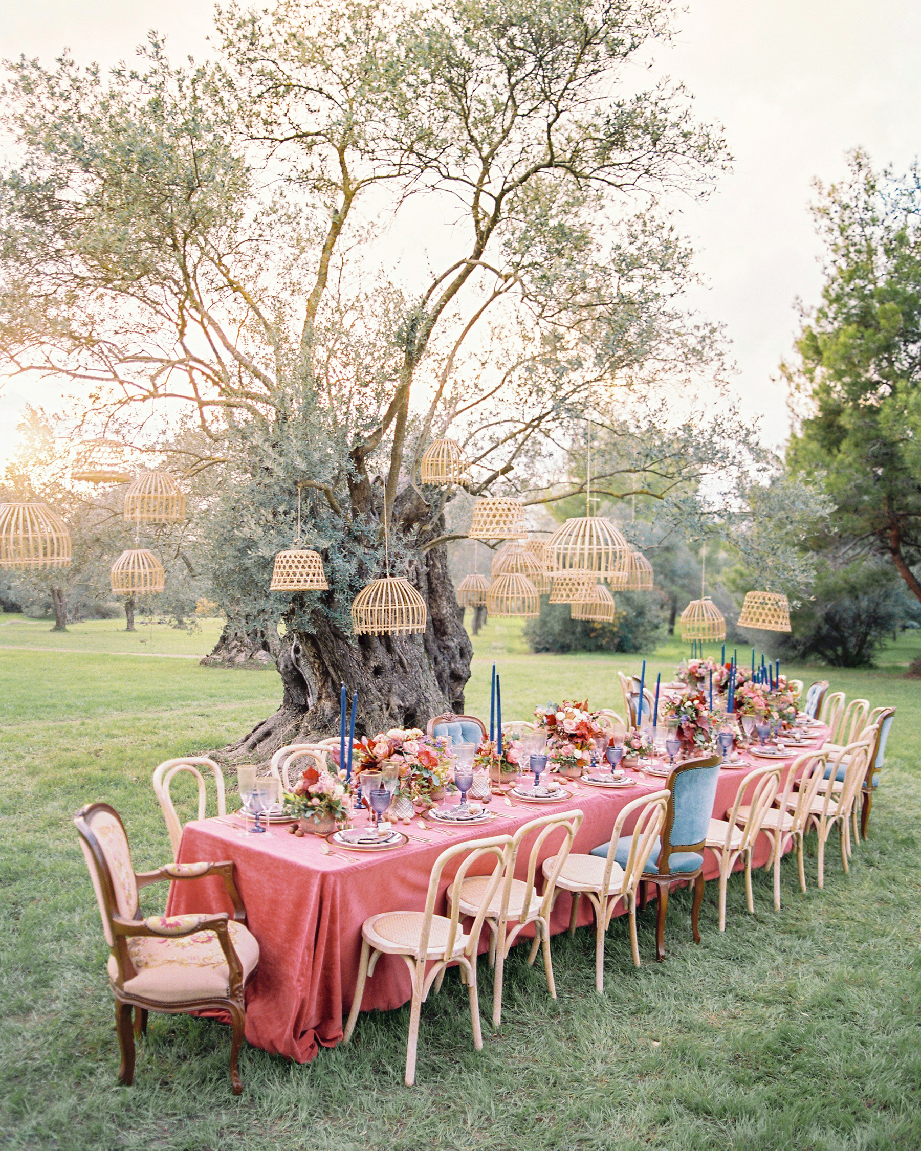 outdoor reception table with wooden lanterns hanging from tree