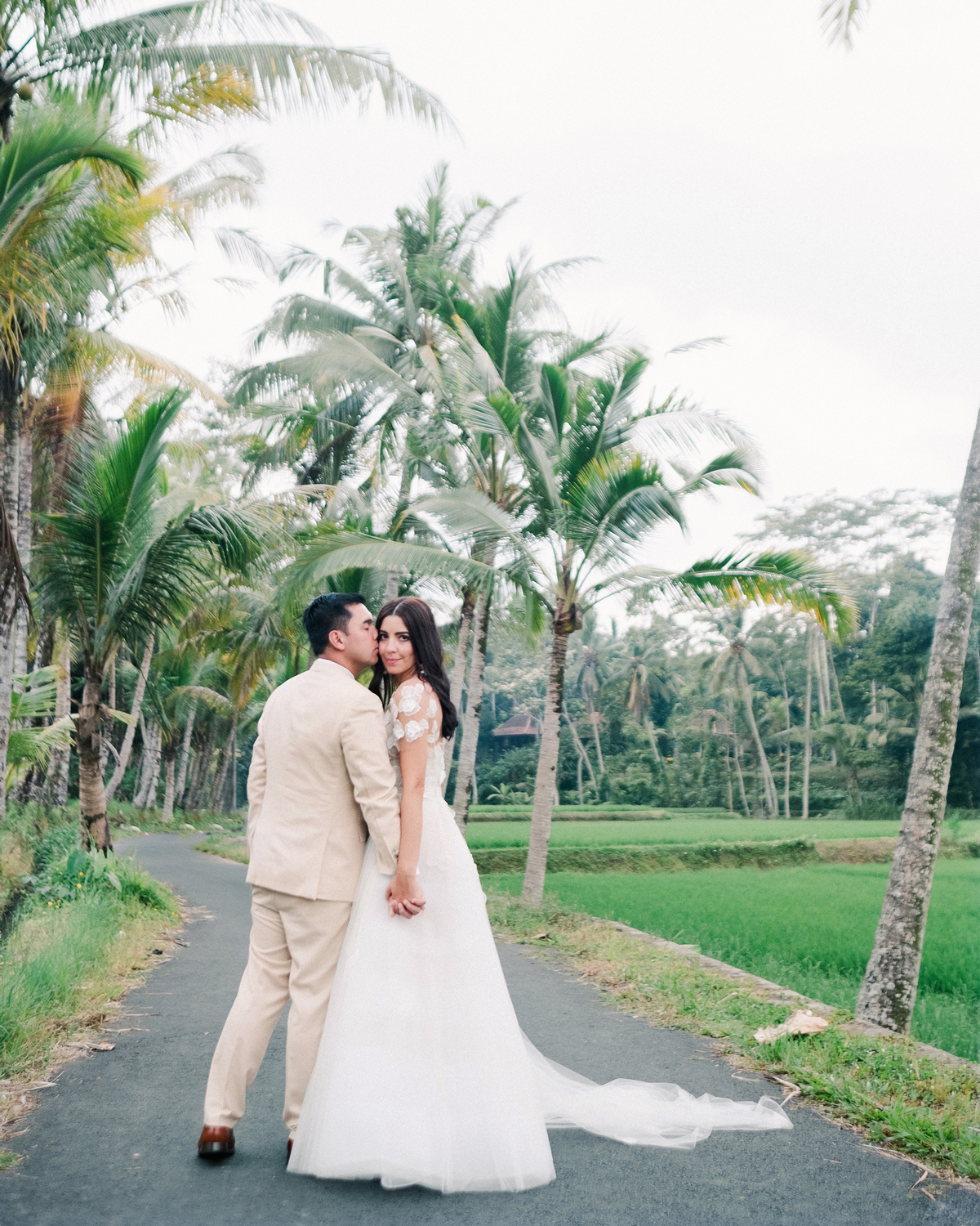 bride and groom holding hands walking along path of palm trees