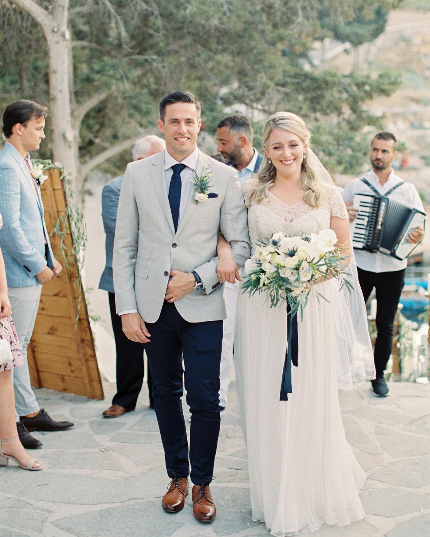 bride and groom interlocking arms walking down aisle