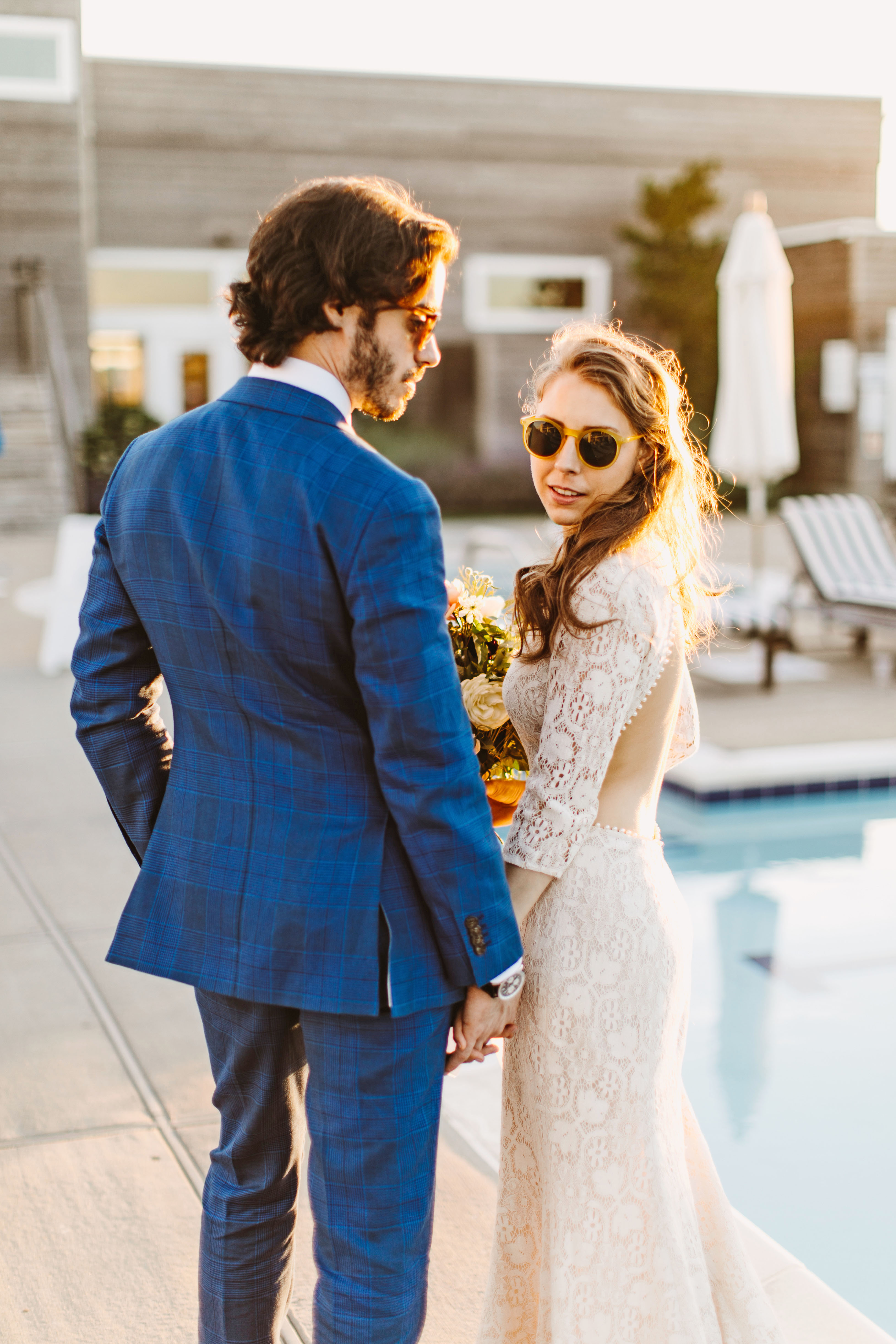 couple wearing sunglasses poolside