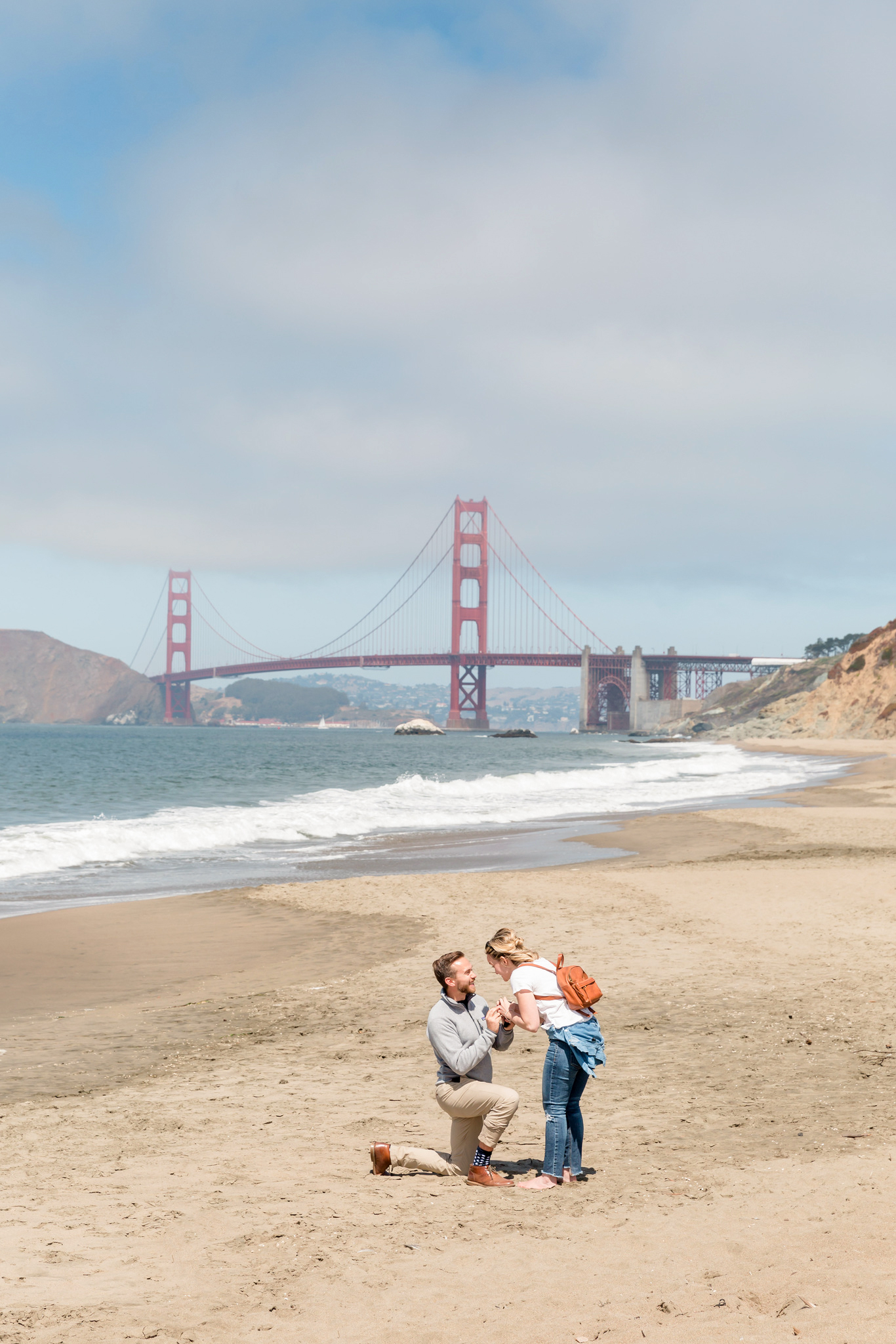 man proposing to girl on beach near golden gate bridge