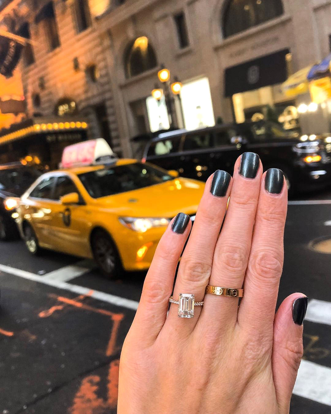 engagement ring selfie cityscape with yellow taxi cab in background