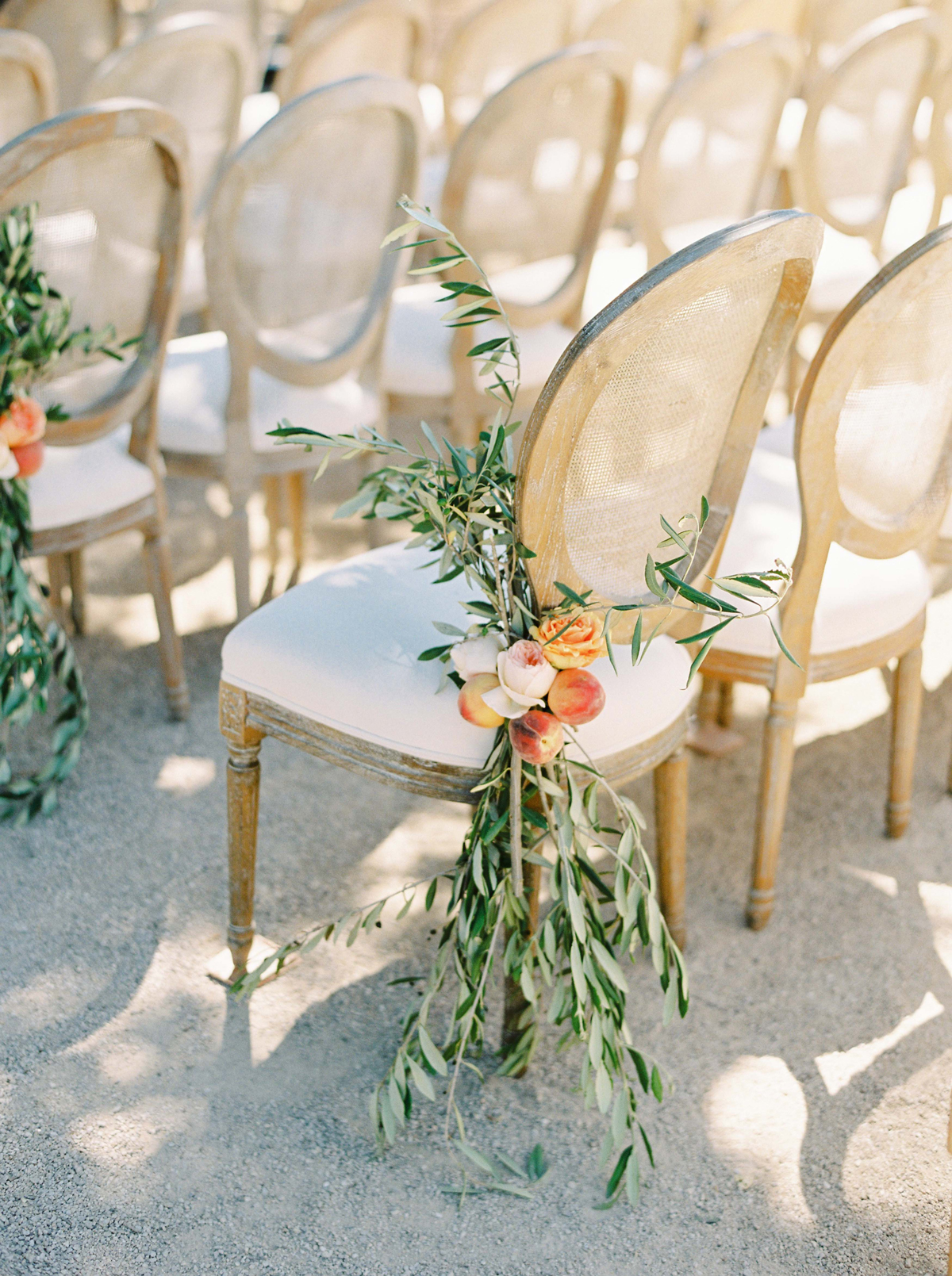 outer aisle chairs decorated with roses peaches and olive branches