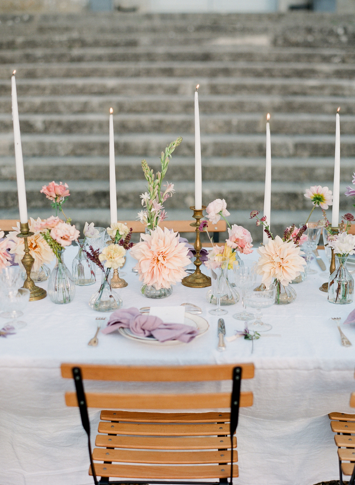 cluster of pink flowers and brass candle sticks