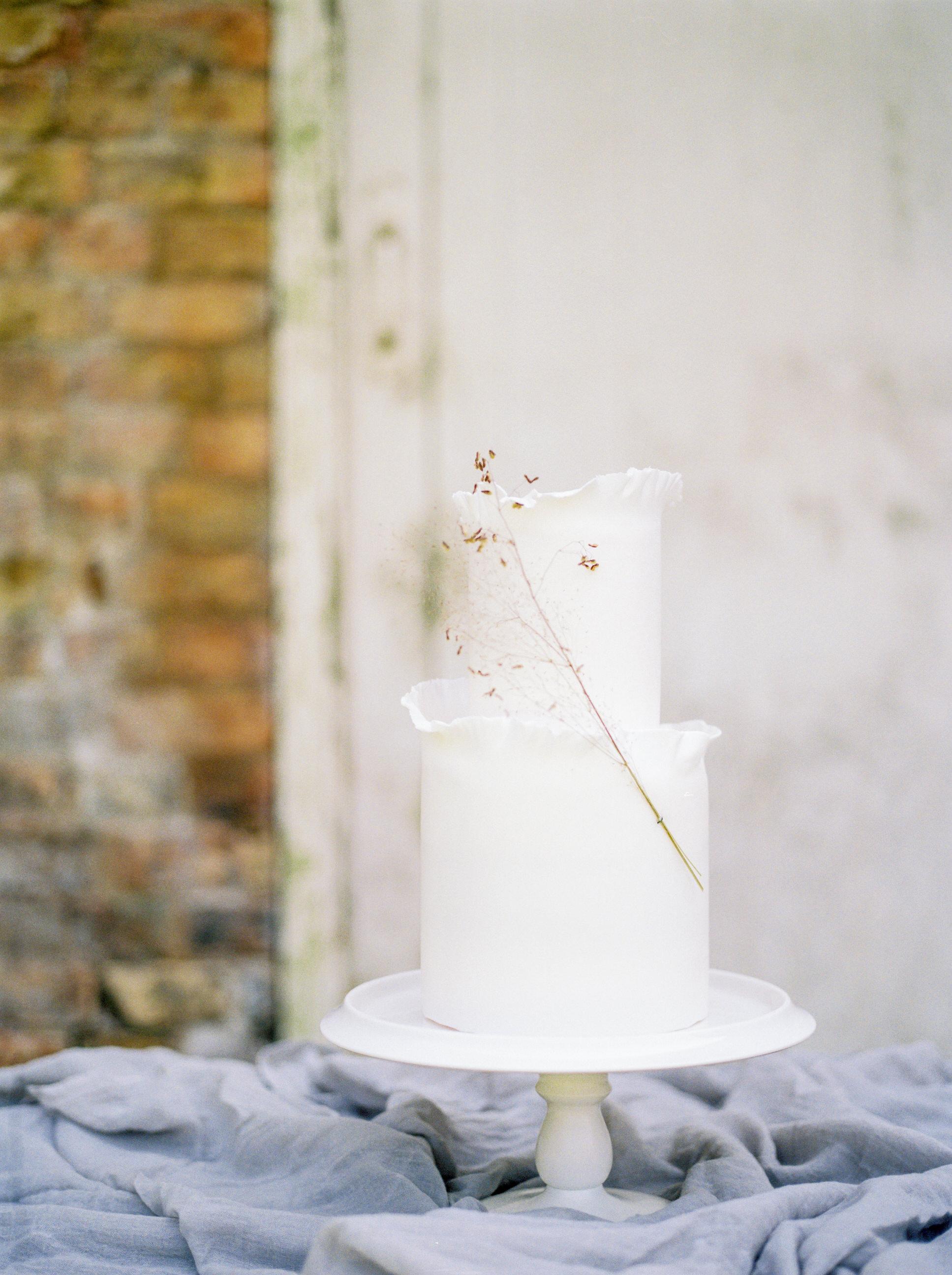 white wedding cake adorned with smokebrush sprig