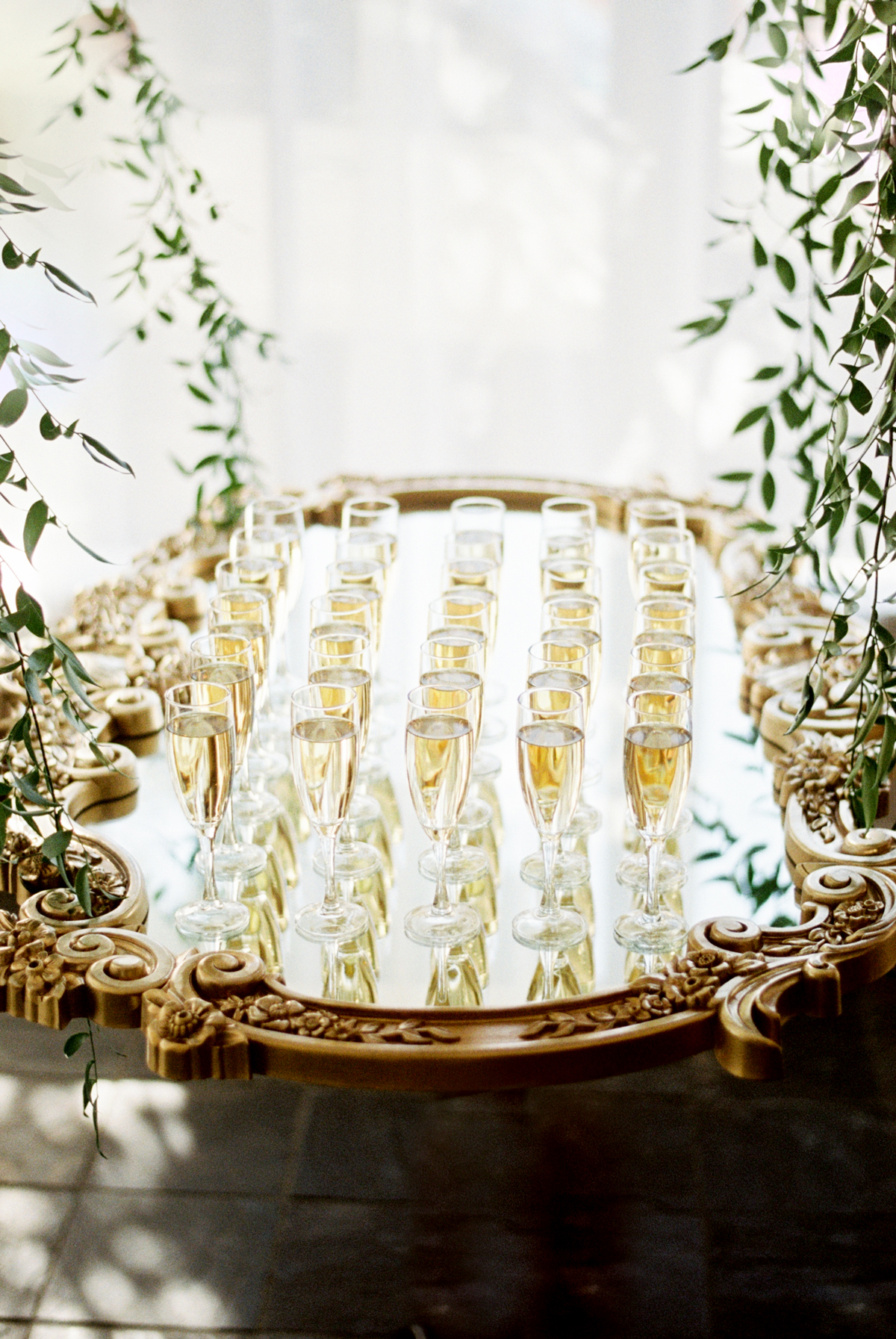 gold framed mirror serving tray with champagne glasses