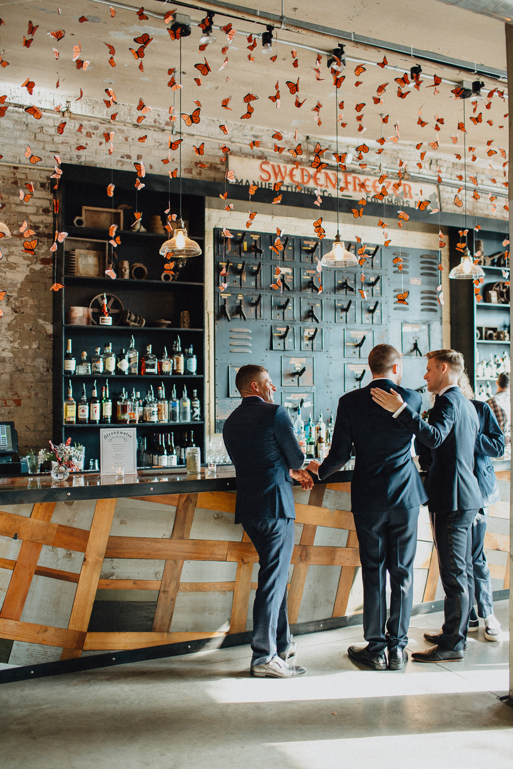 groomsmen standing by bar decorated with butterflies
