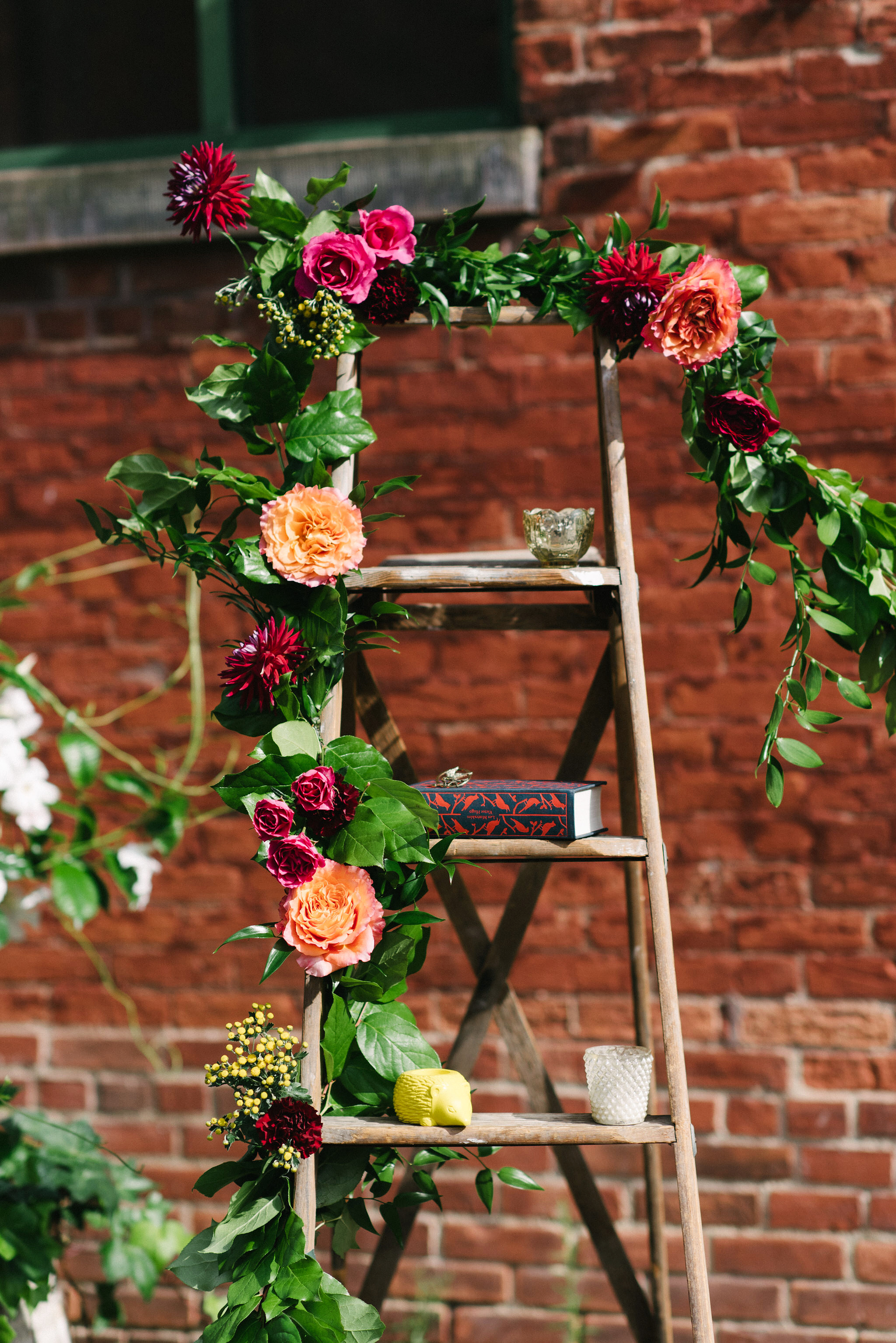 steph tim wedding ceremony ladder brick and flowers backdrop