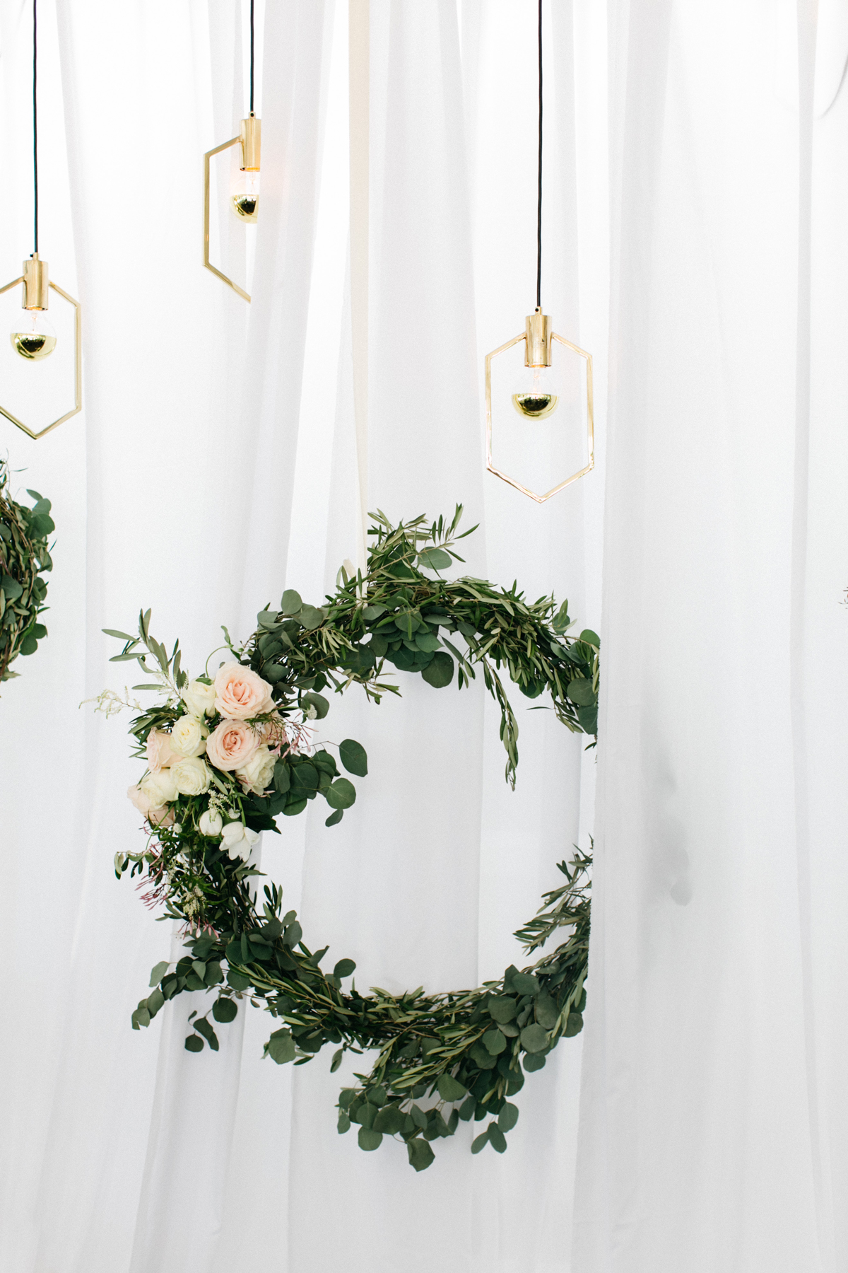 wedding wreaths foliage and roses hanging by exposed light bulbs