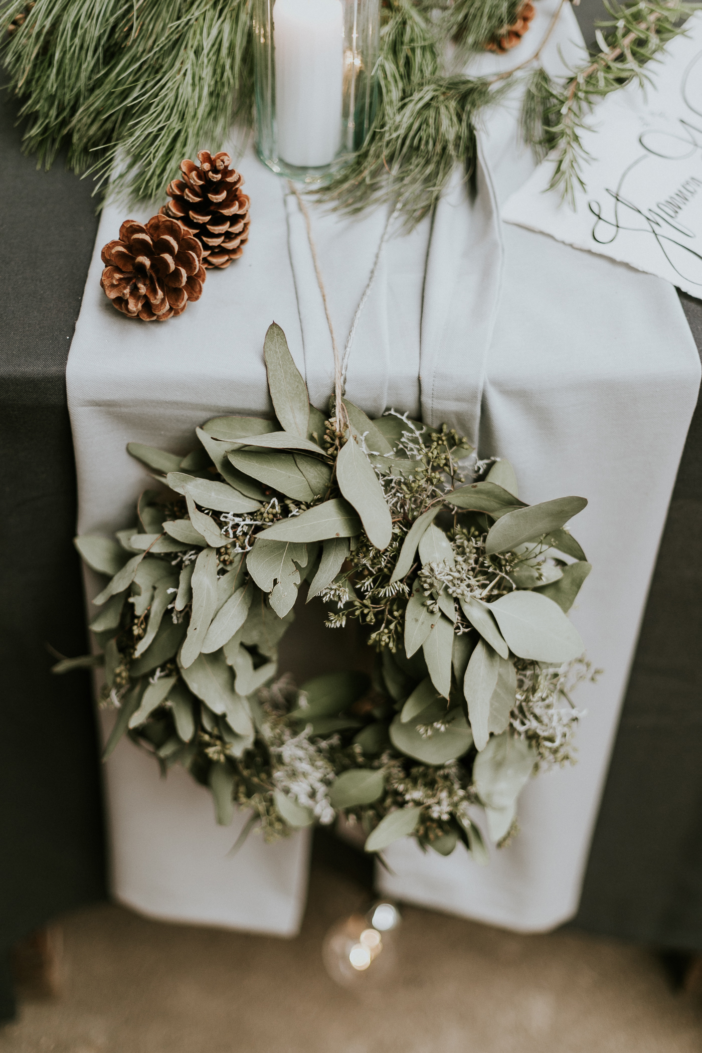 wedding wreath hanging from table with pine cones