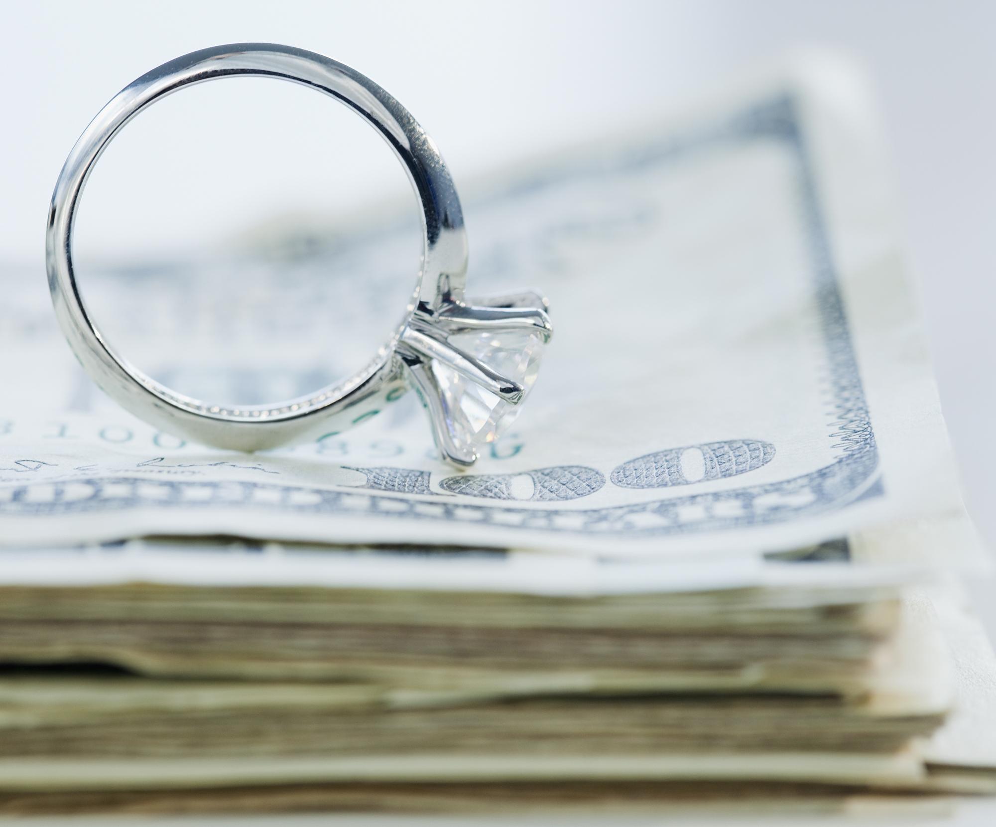 engagement ring sitting on money
