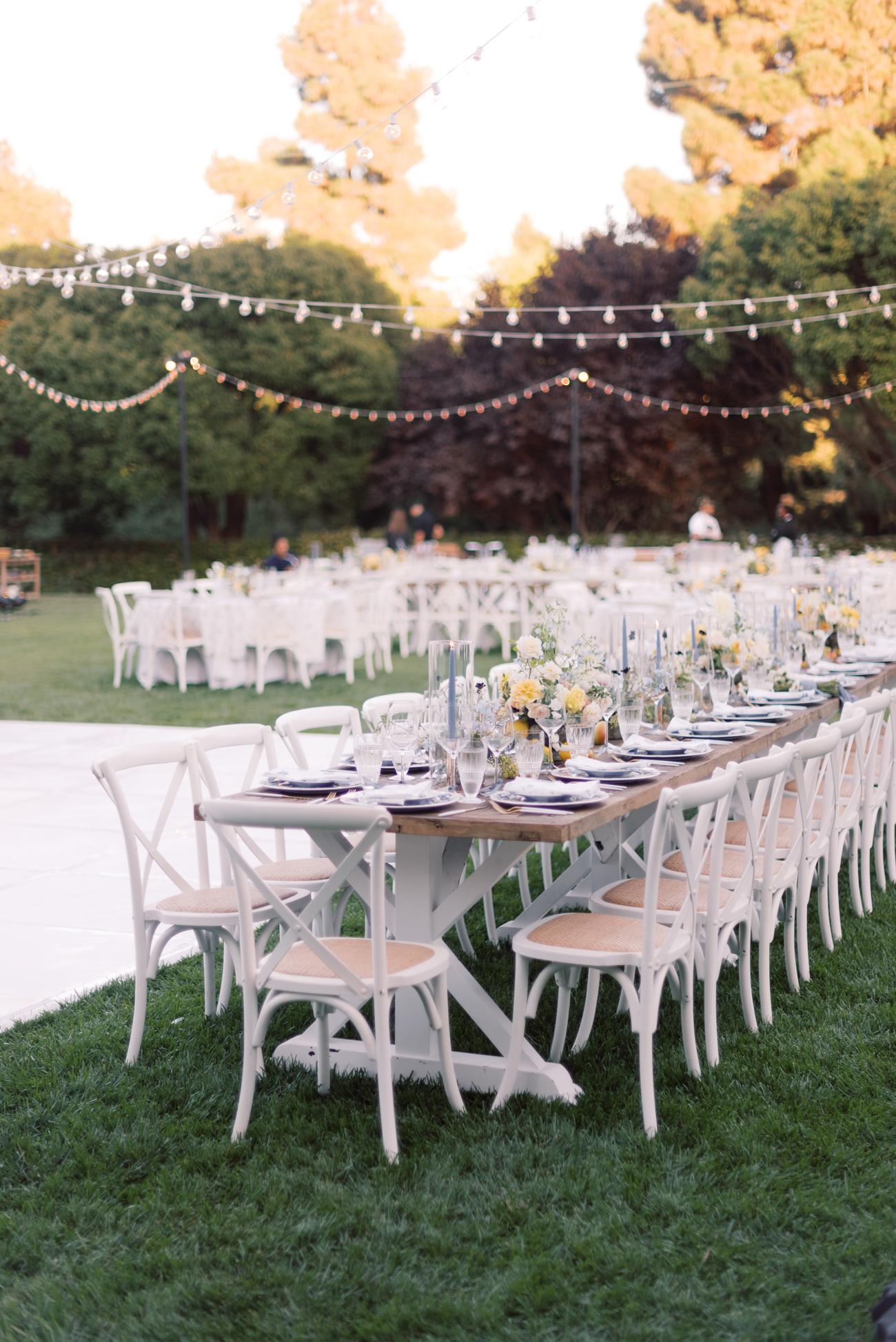wooden table string light outside wedding reception setup