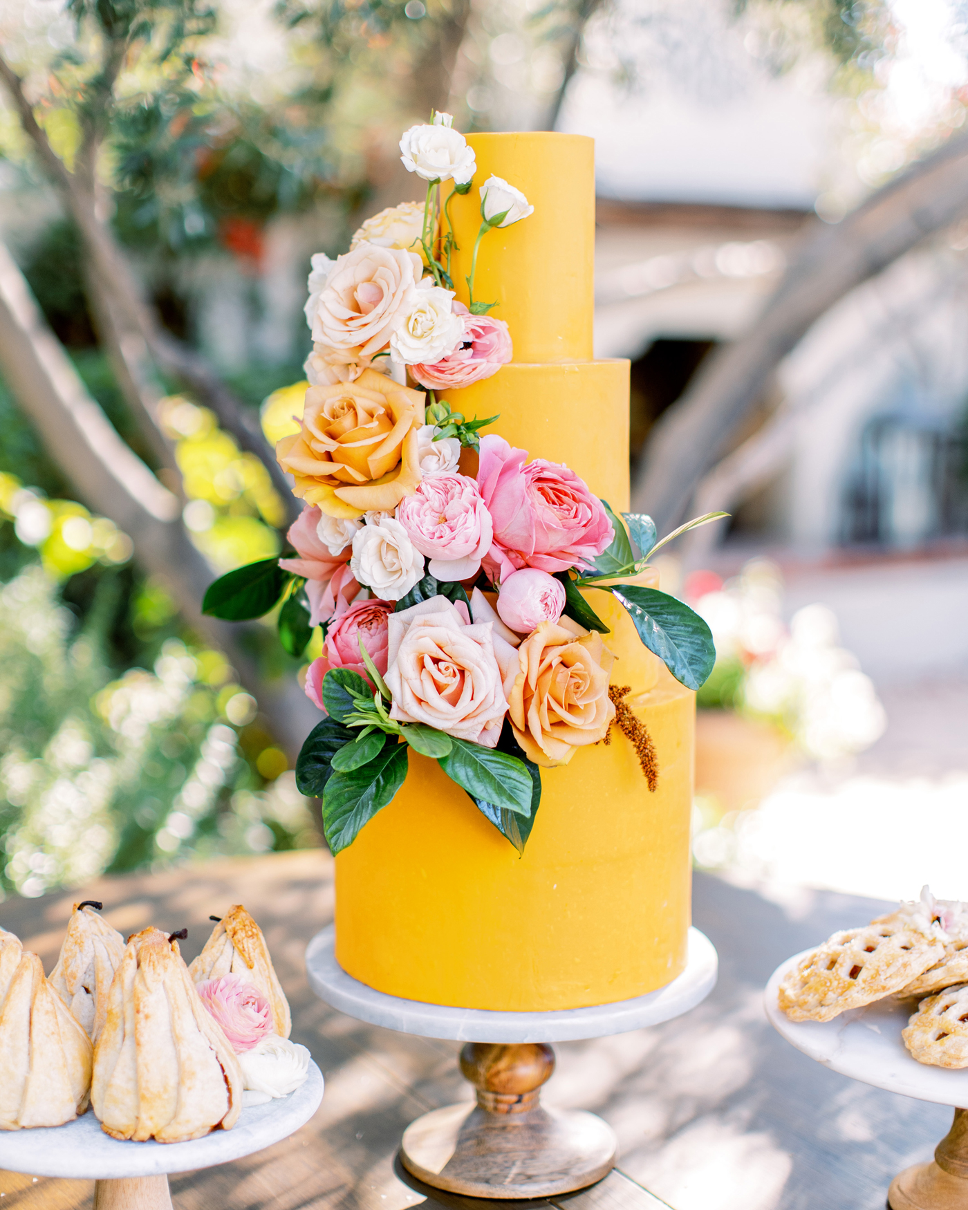 four tiered deep golden yellow frosted wedding cake with floral display