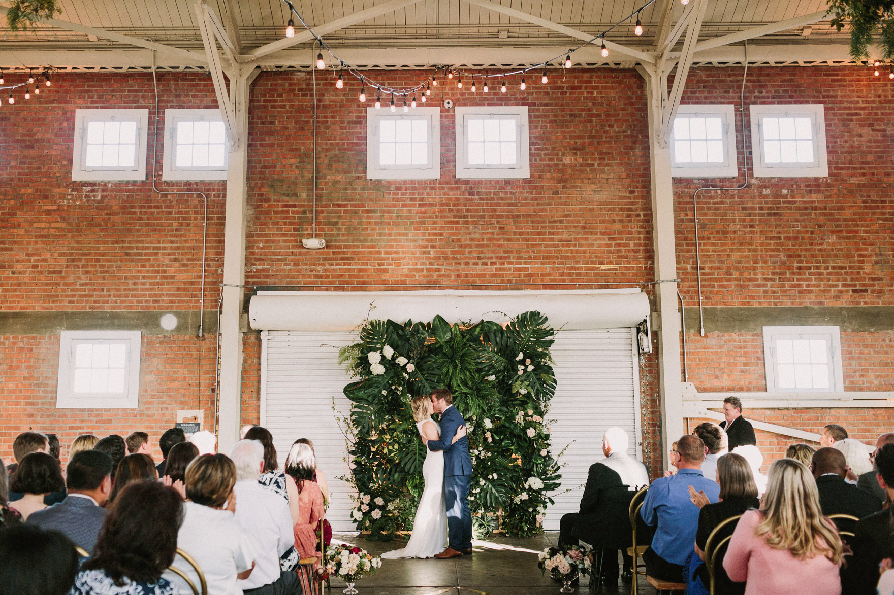 tropical greenery wedding ceremony backdrop pink white blooms