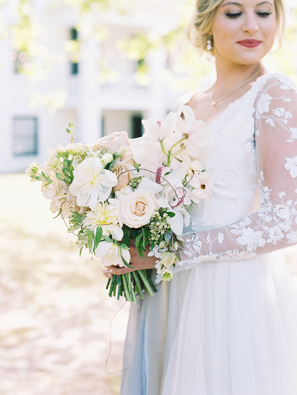 bride wearing lace long-sleeved gown holding neutral and green bouquet