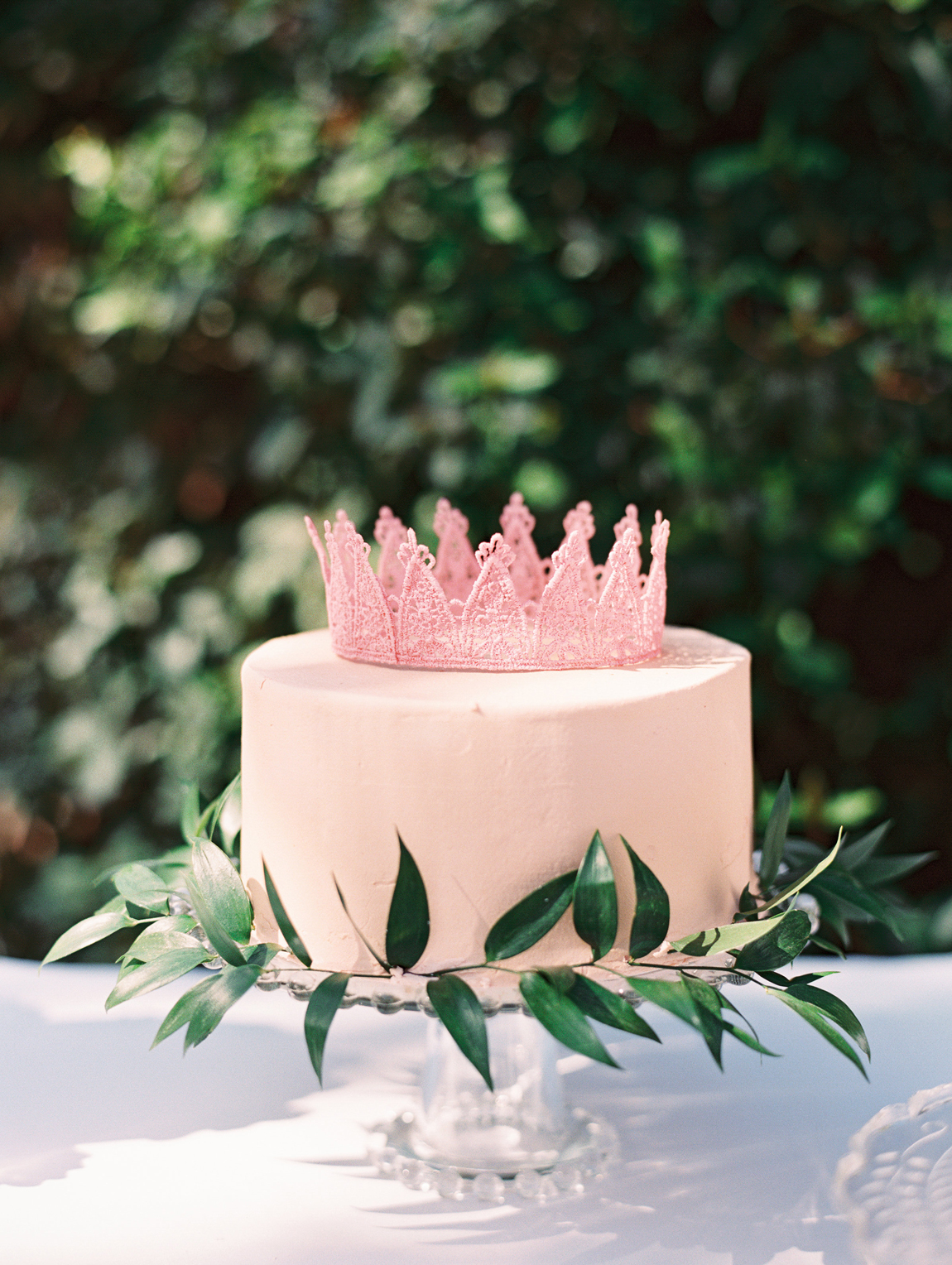 pink lace crown single layered pink frosted cake with greenery accent