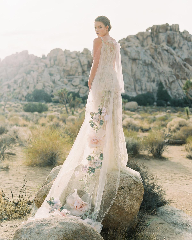 bride wearing long train lace wedding dress outside standing on rock with flowers