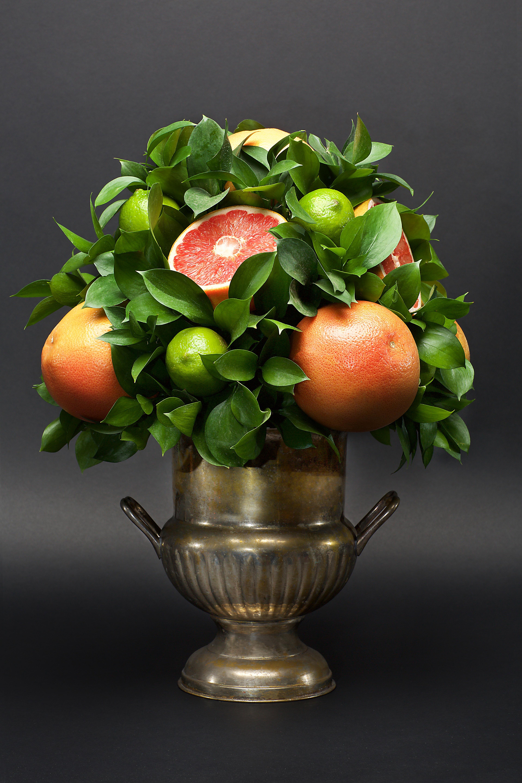 citrus centerpiece grapefruit limes leaves silver vase