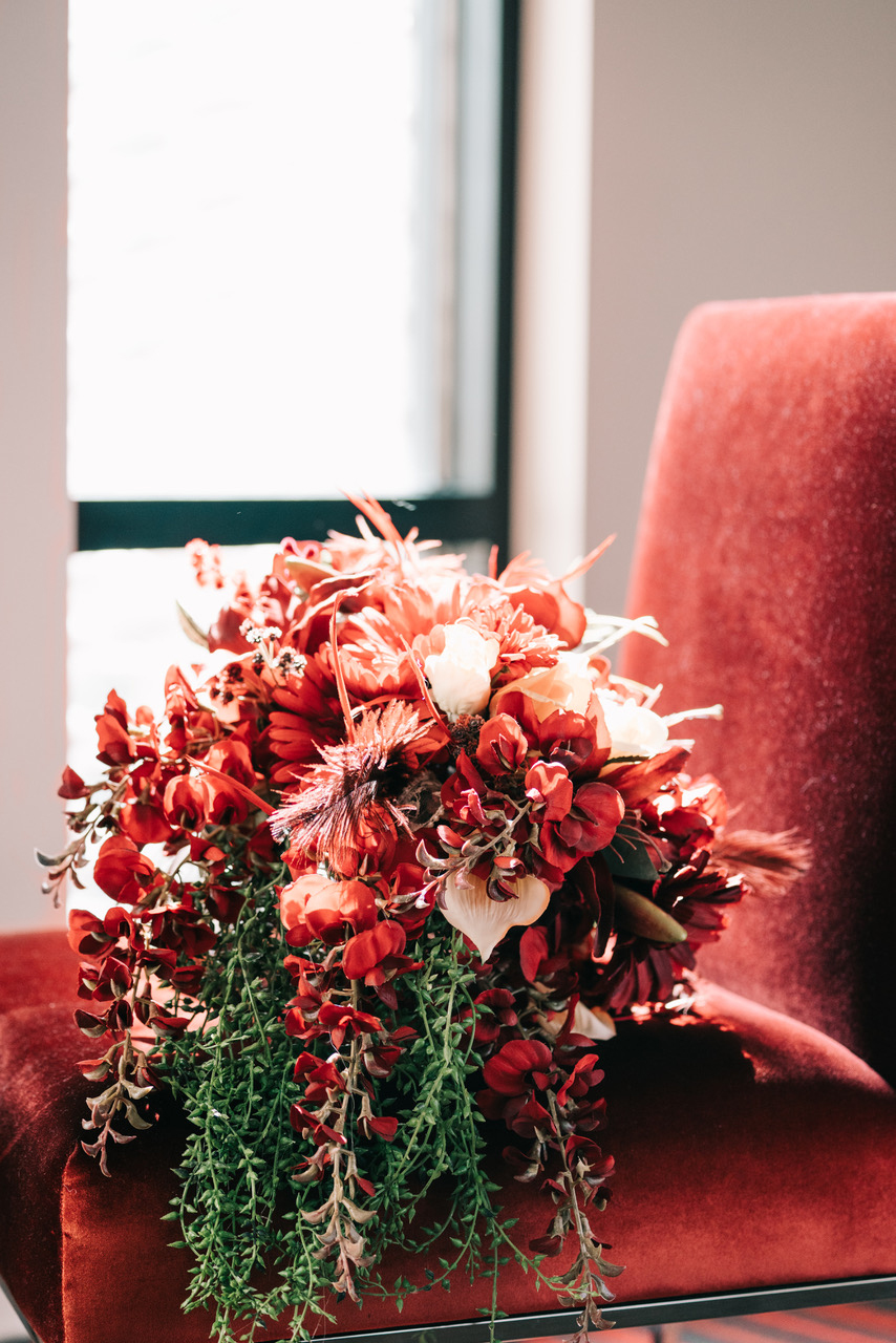 unique wedding color palette red chair by window red bouquet