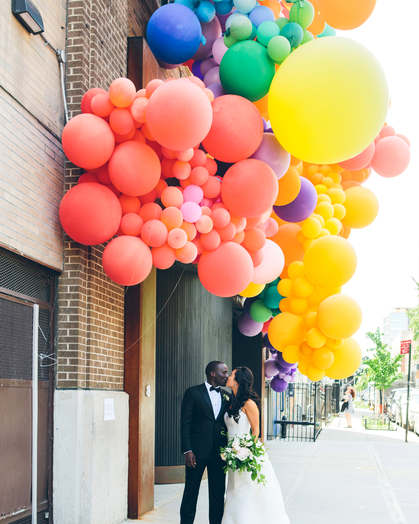 bride and groom kissing under various sized rainbow-hued balloons