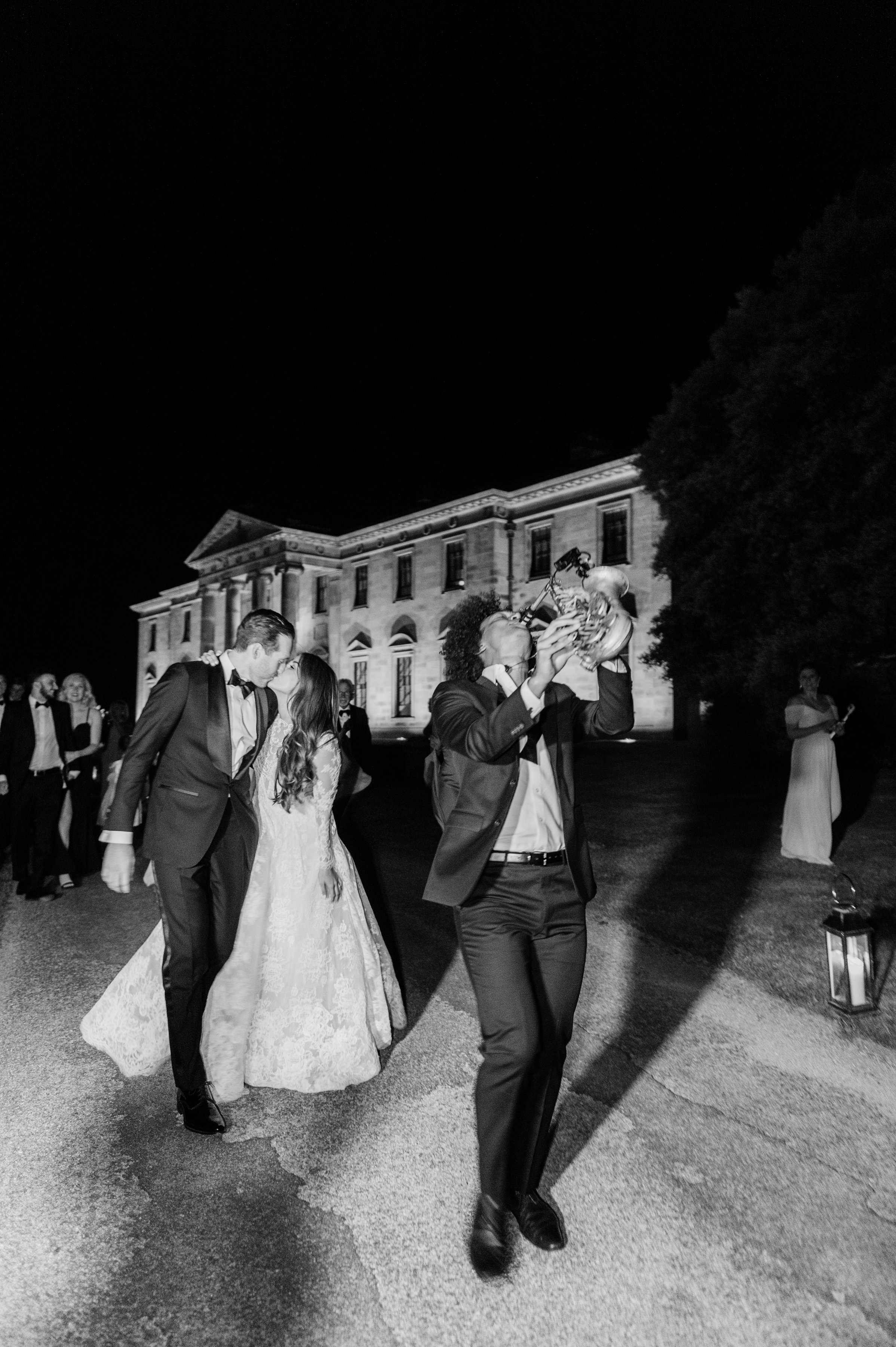 bride and groom kissing while saxophonist plays