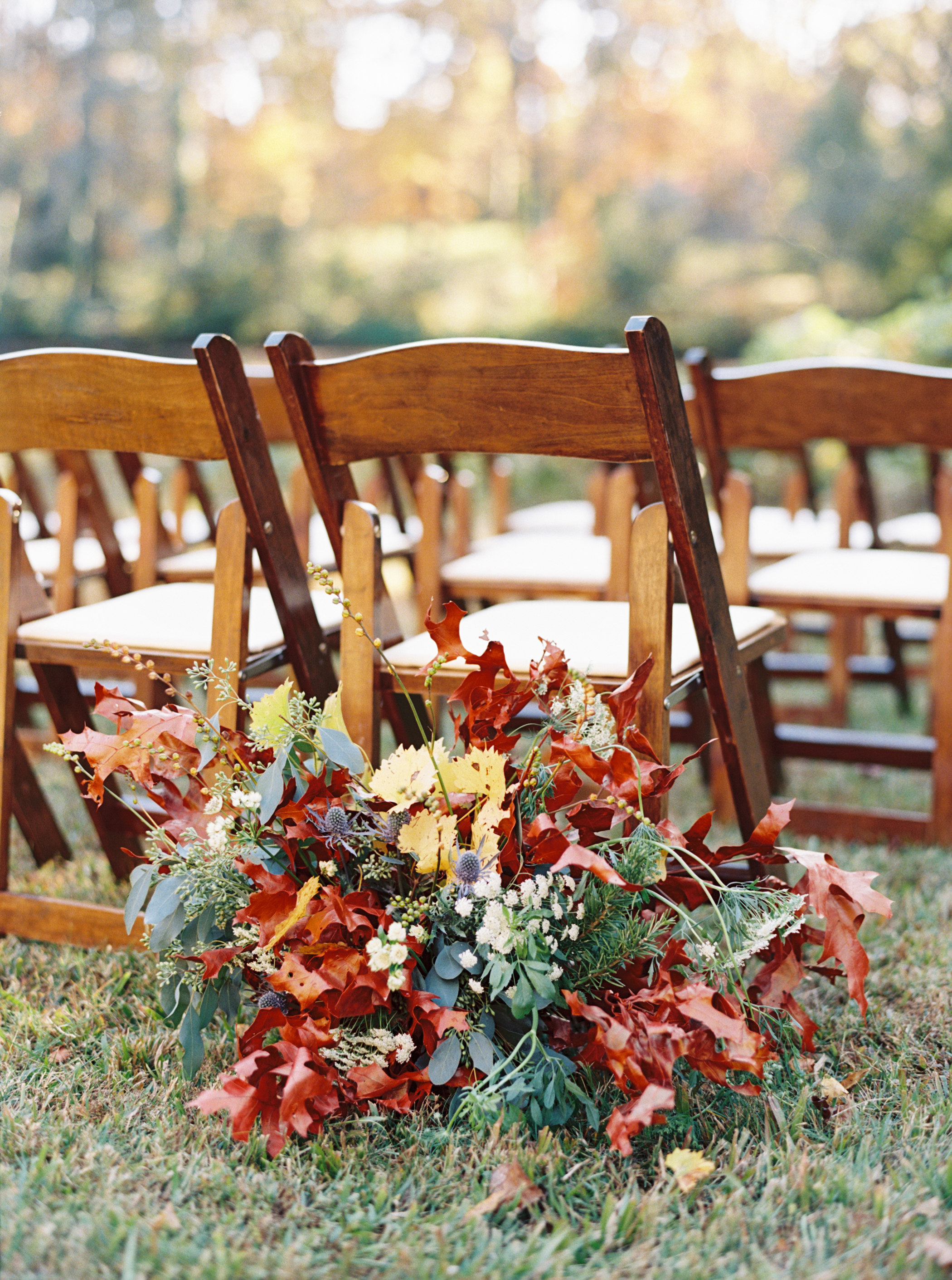 Colorful fall leaf arrangement behind chair