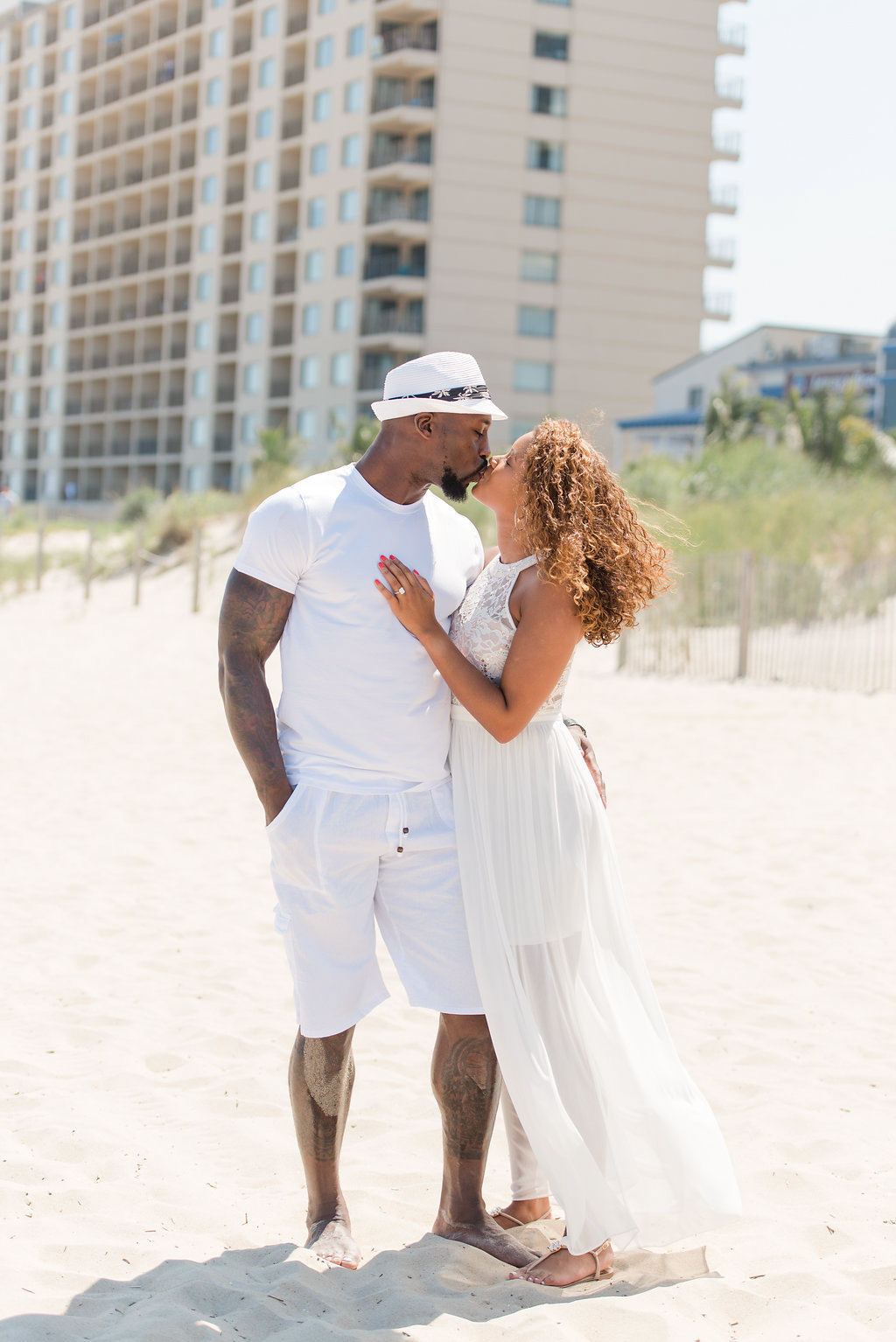 couple wearing white kissing on beach