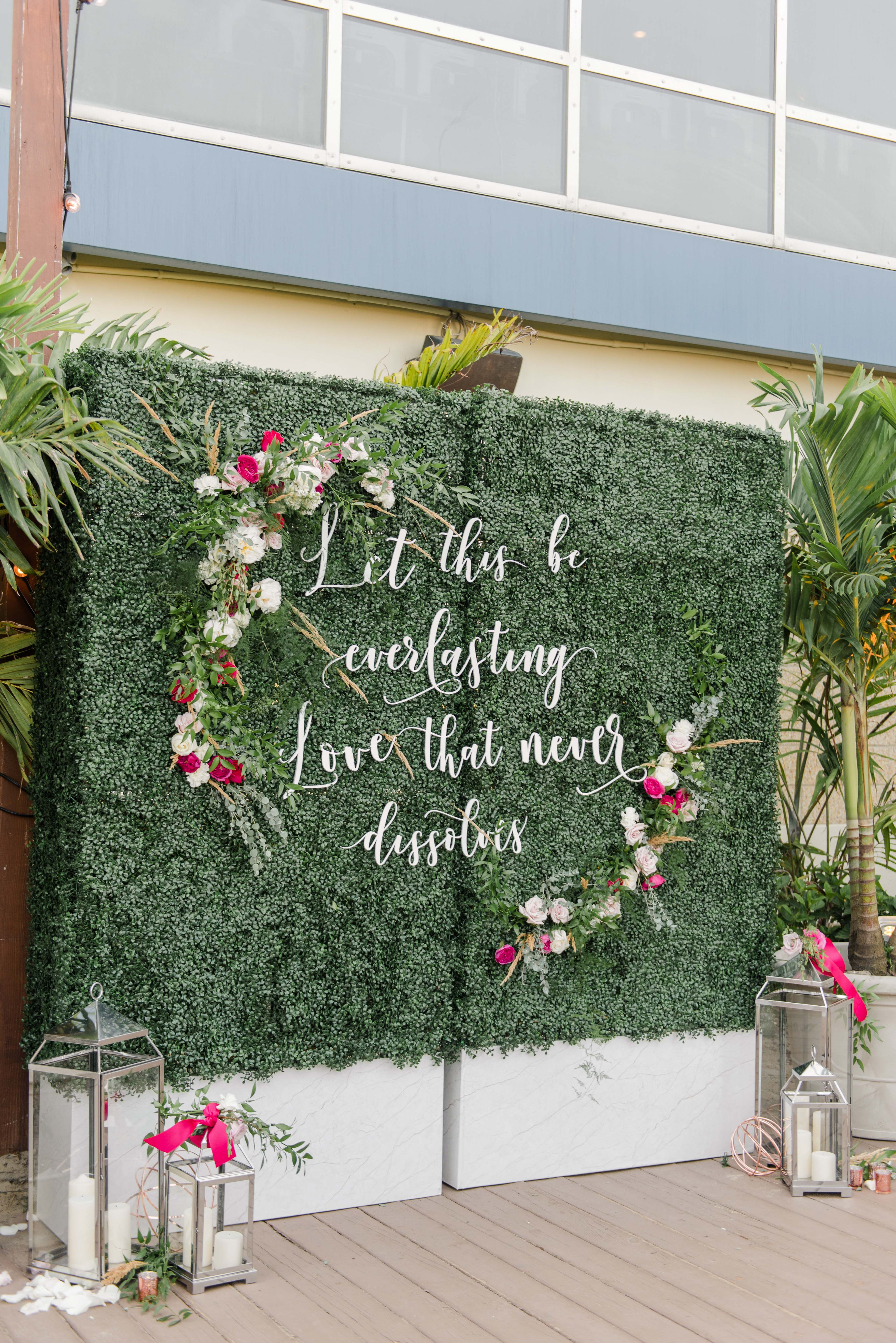 boxwood wall with fresh flowers and cut out letters