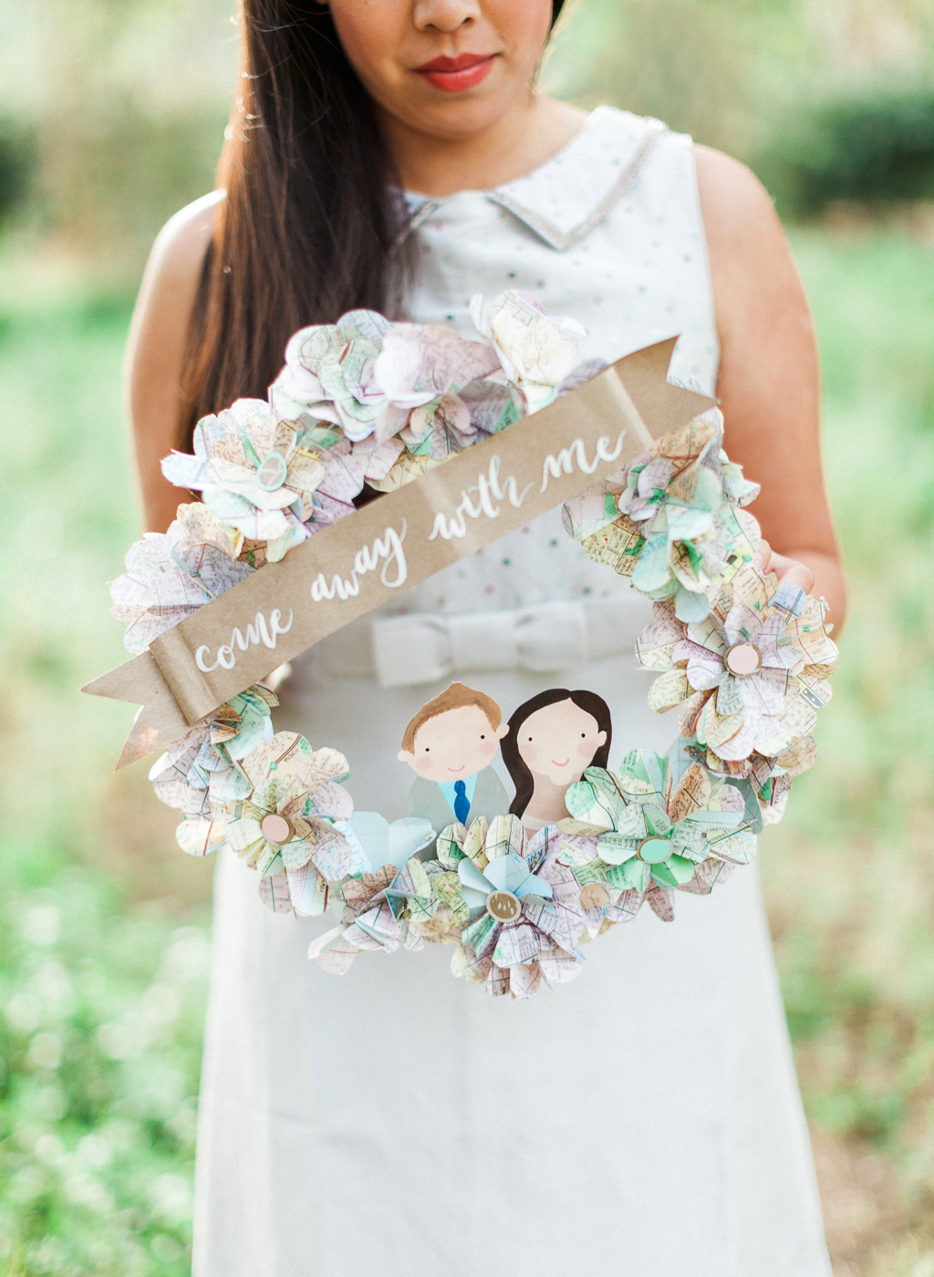 woman holding paper wreath that reads come away with me