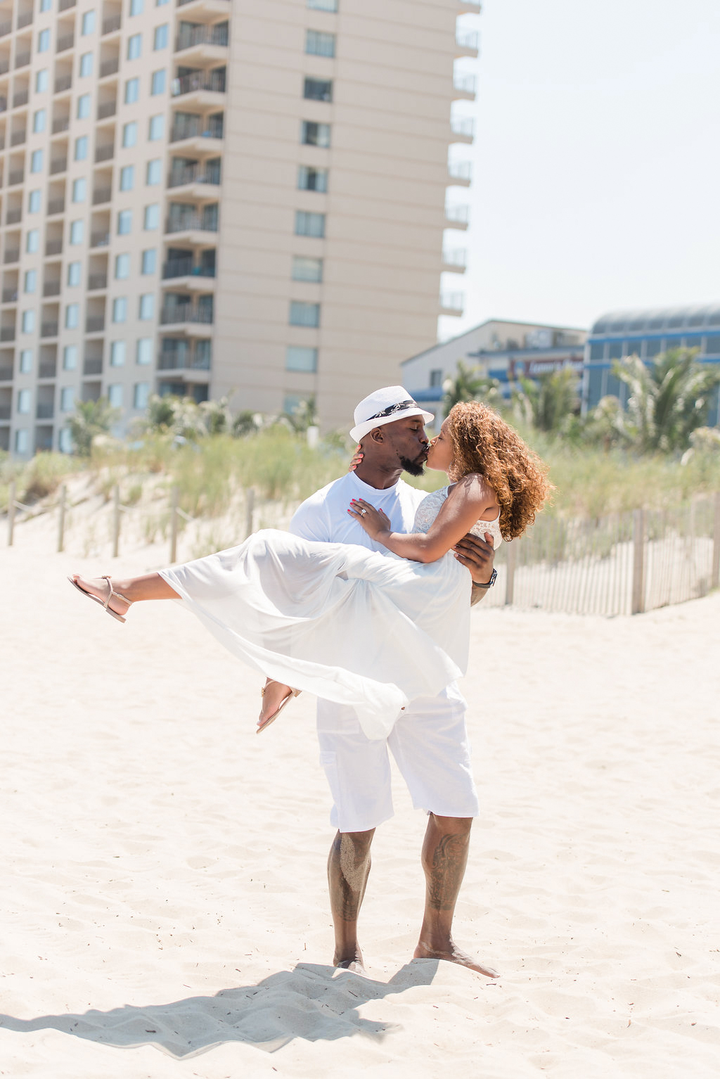 man carrying wife kissing on beach