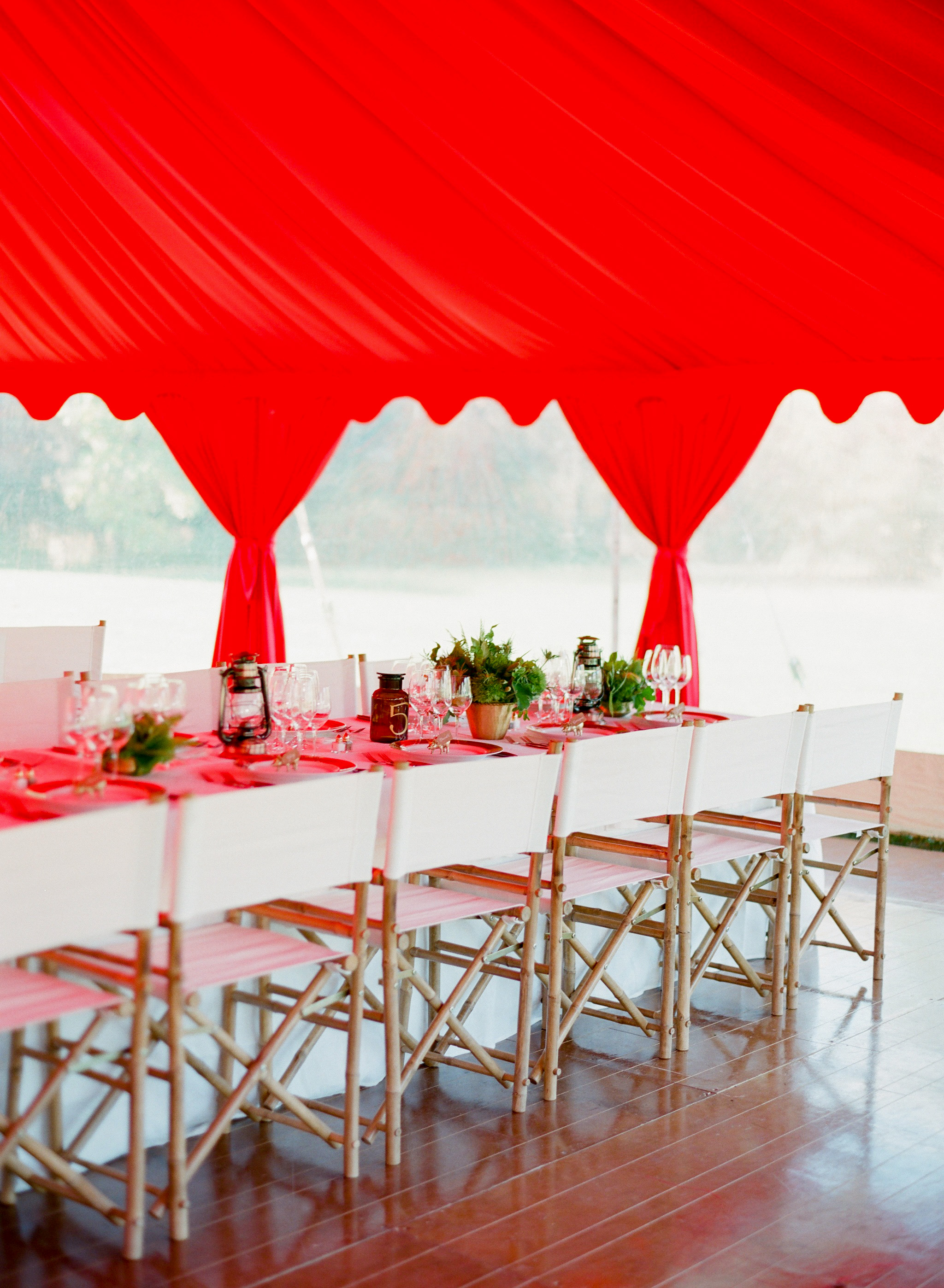 winter rehearsal dinner table with red drapers and white chairs
