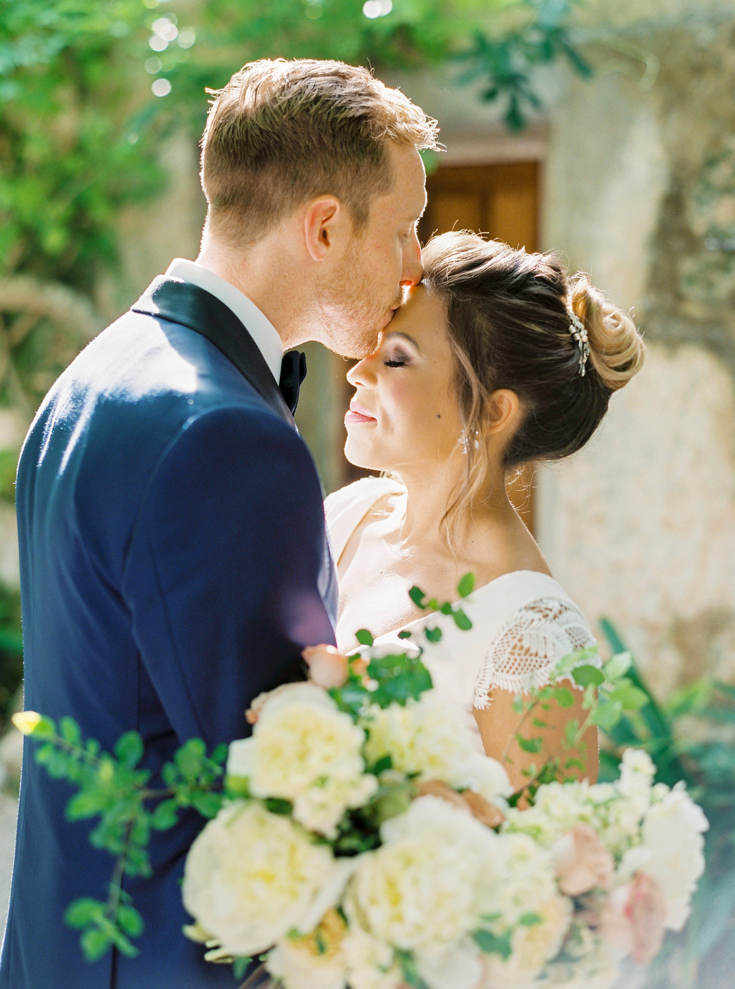 wedding couple groom kissing brides forehead with flowers