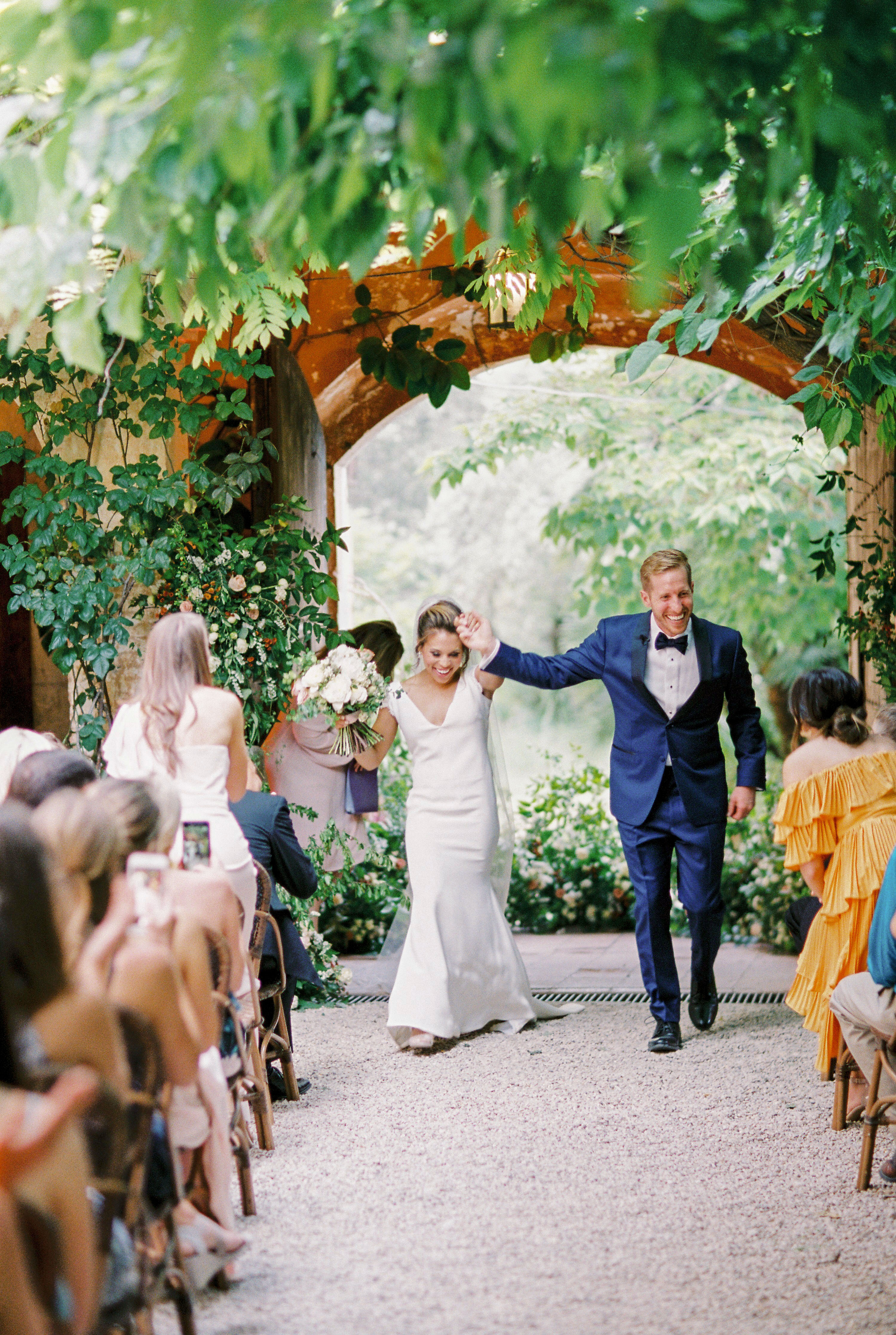 real weddings ceremony recessional happy couple hold hands