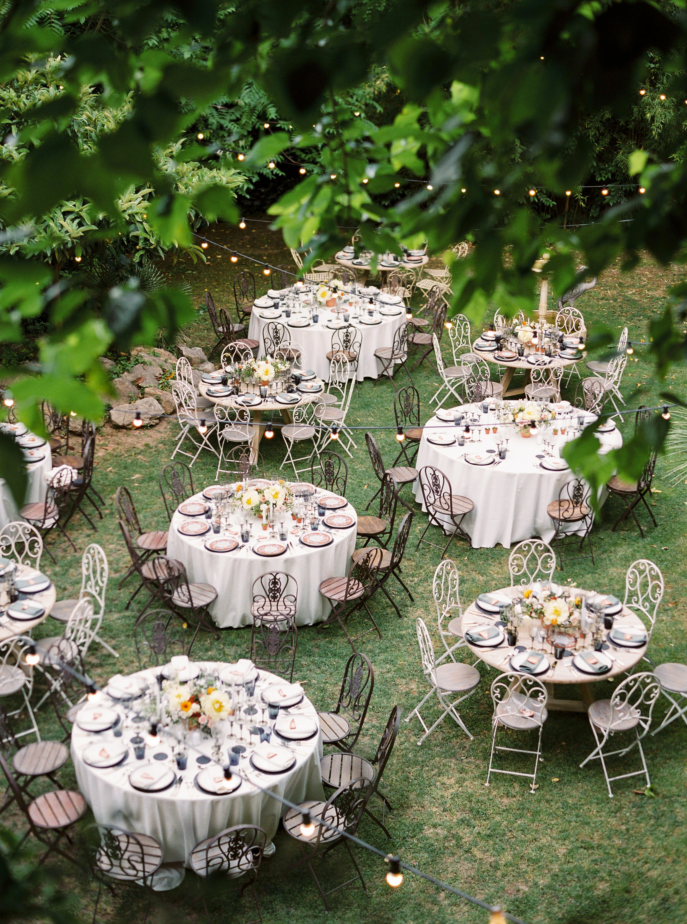 outdoor reception setup with round tables black and white chairs