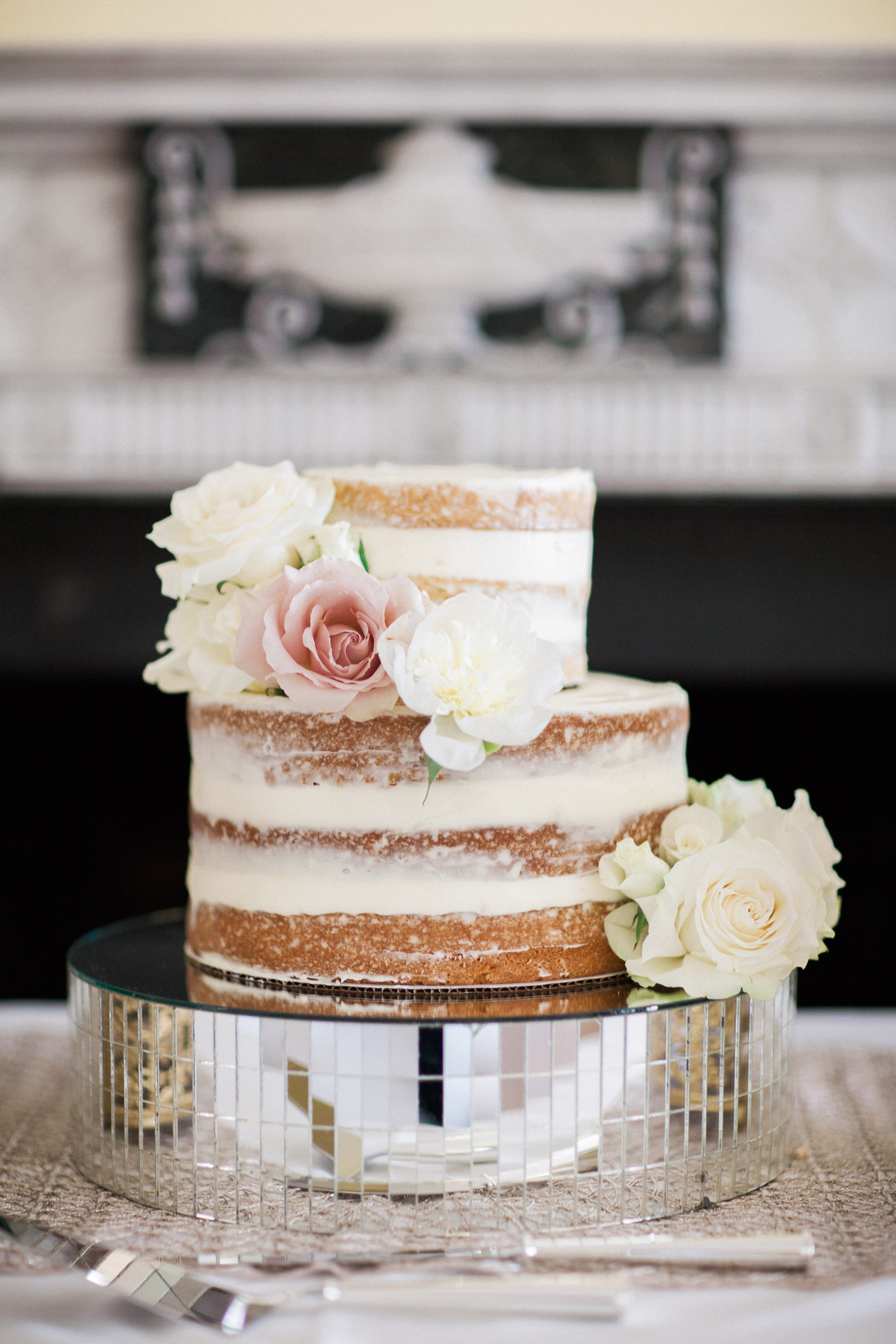 wedding cake sitting on mirrored pieces base