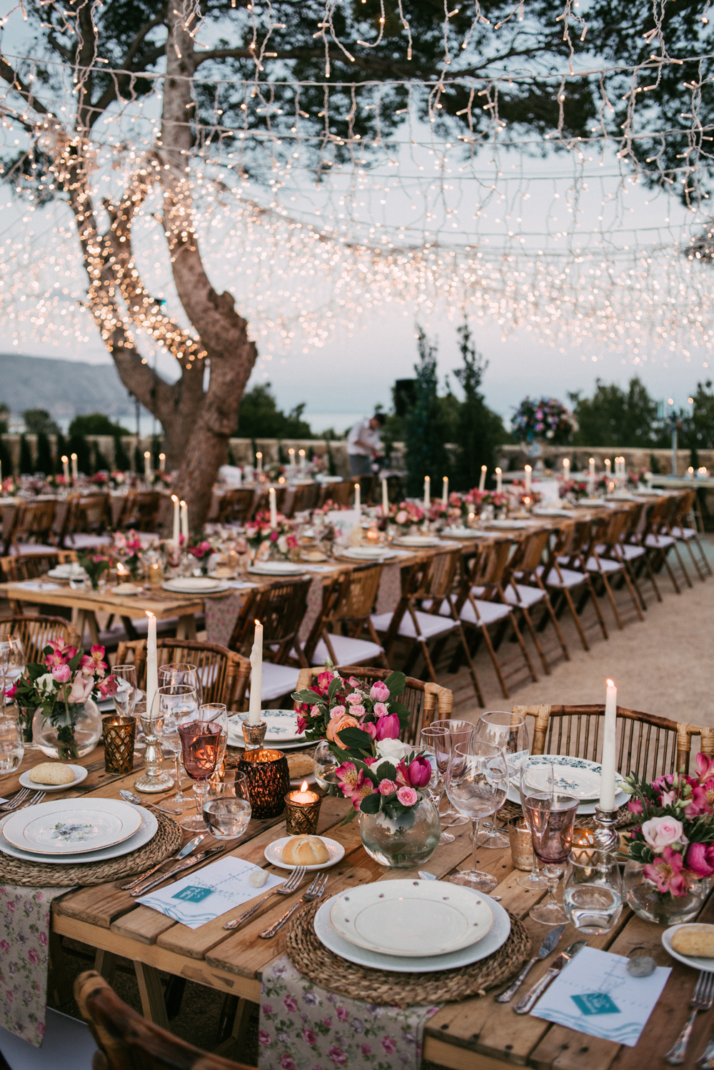 twinkle lights hanging from trees above candlelit reception tables