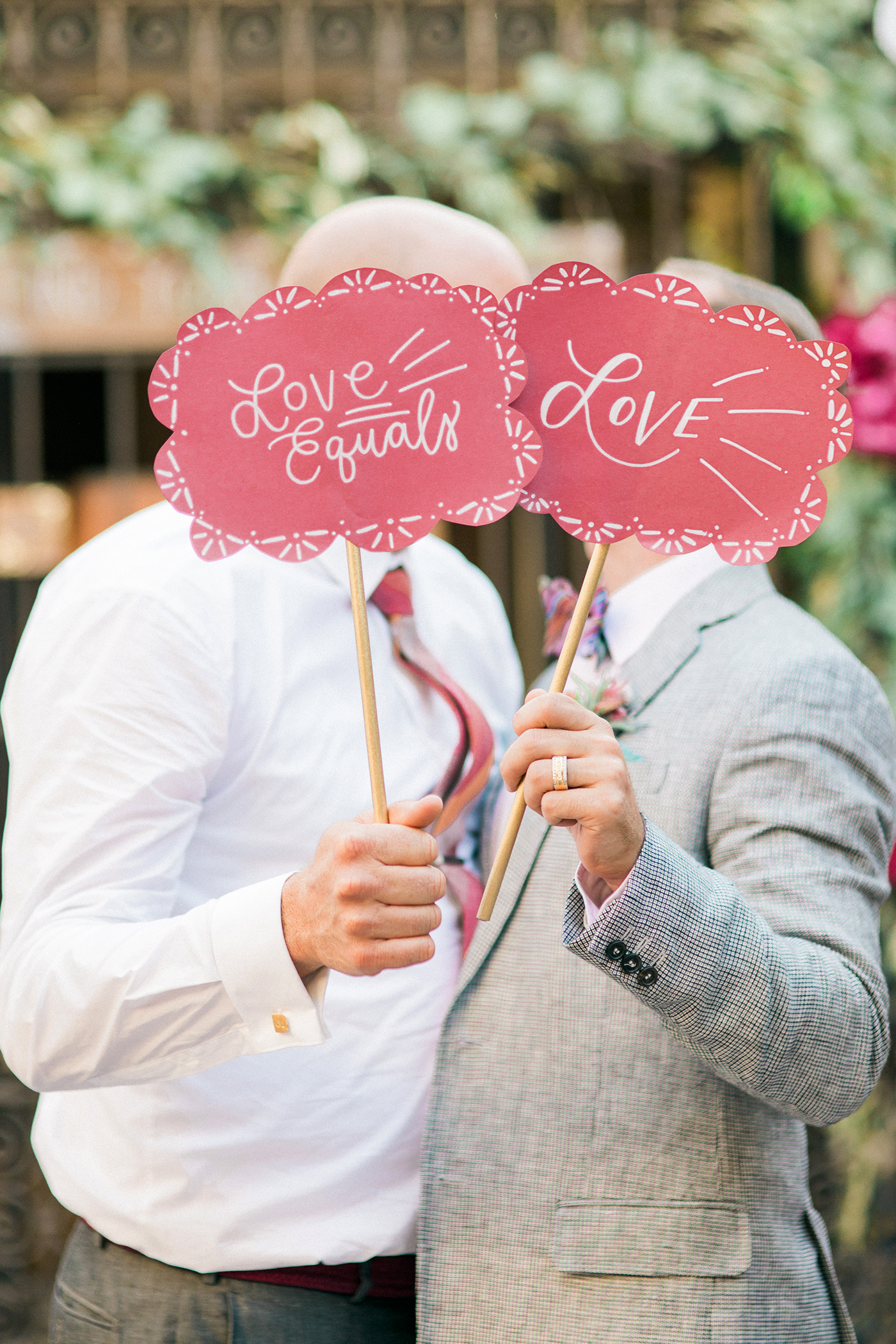 scalloped wedding decor grooms holding love equals love signs